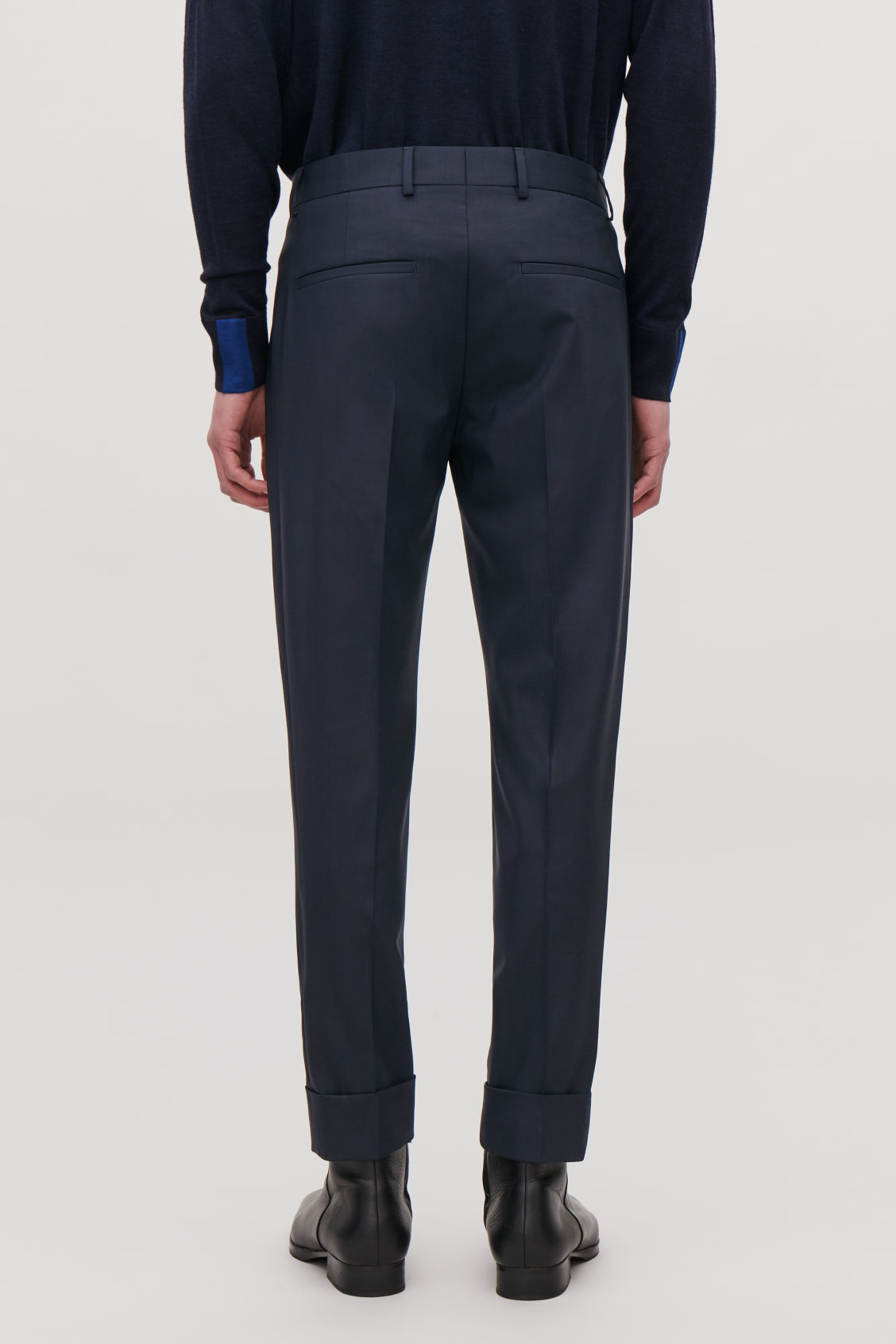 Model side image of Cos slim trousers with side panels in blue