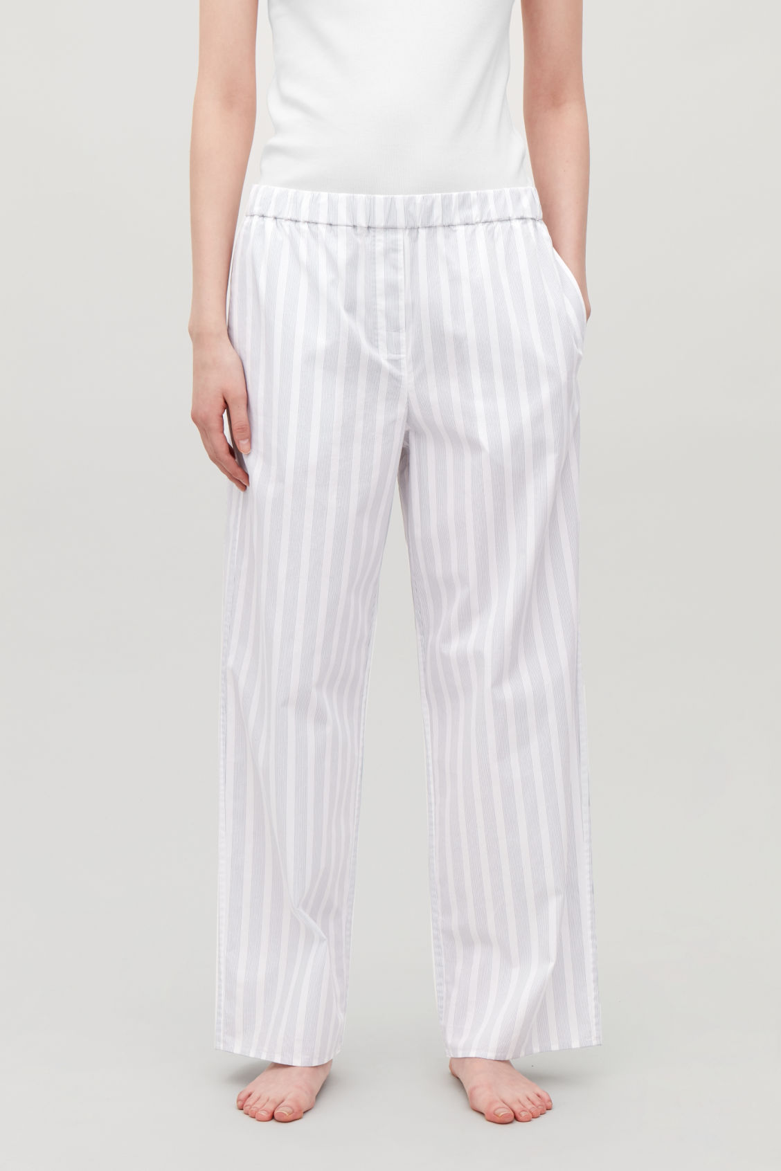 Model side image of Cos striped pyjama trousers in white