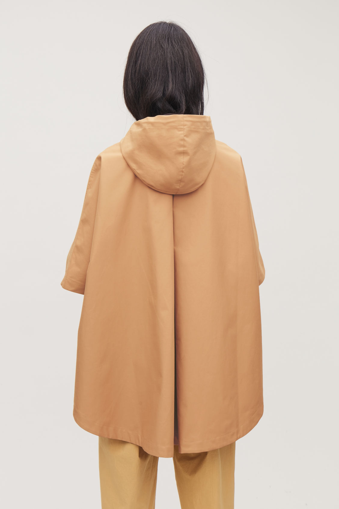 Model side image of Cos hooded poncho with curved hem in beige