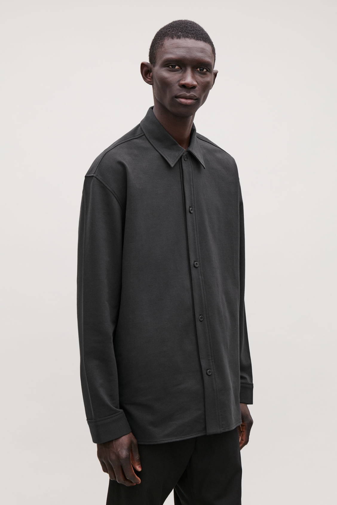 Model side image of Cos relaxed thick-cotton shirt in black