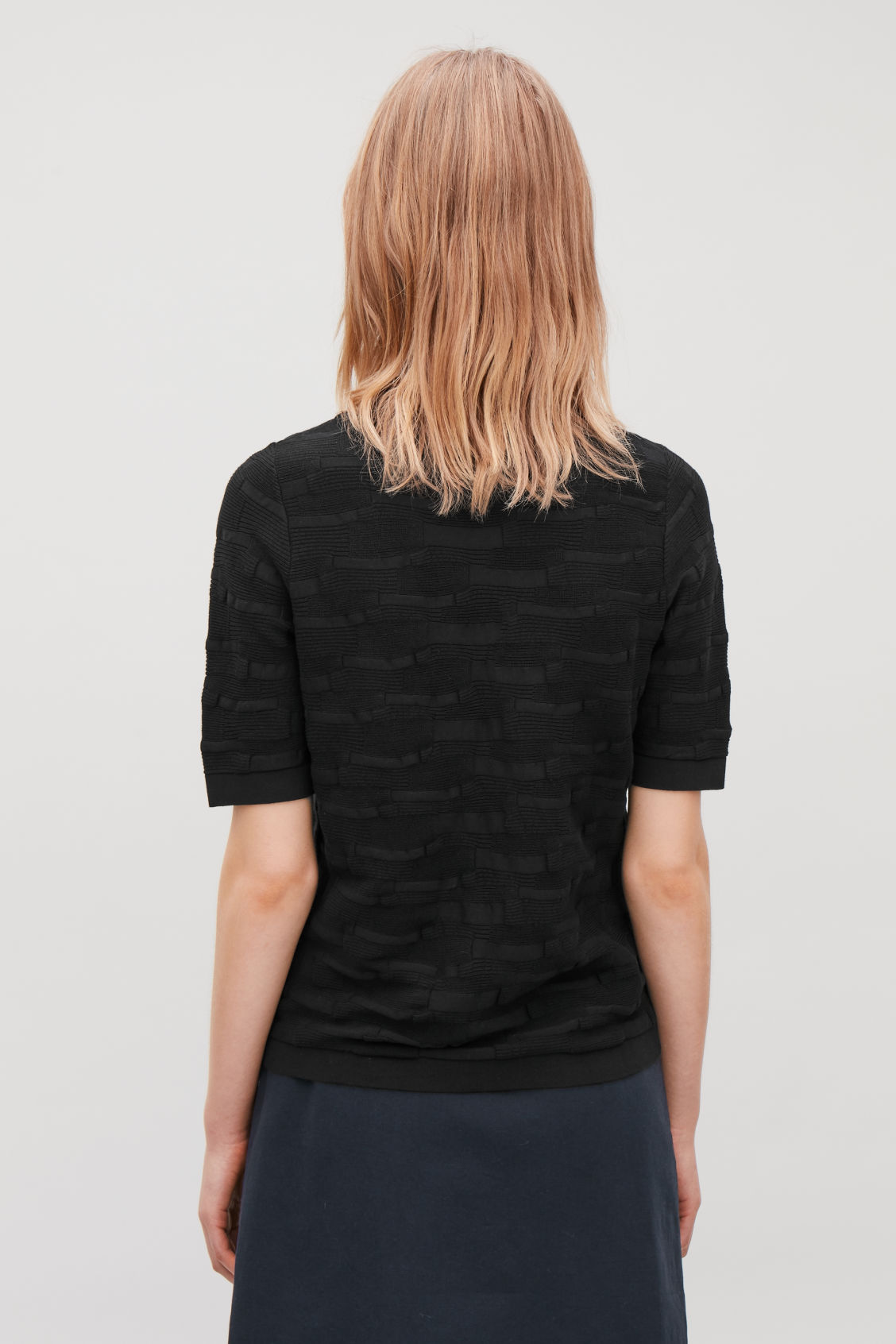 Model side image of Cos irregular-stitch knit top in black