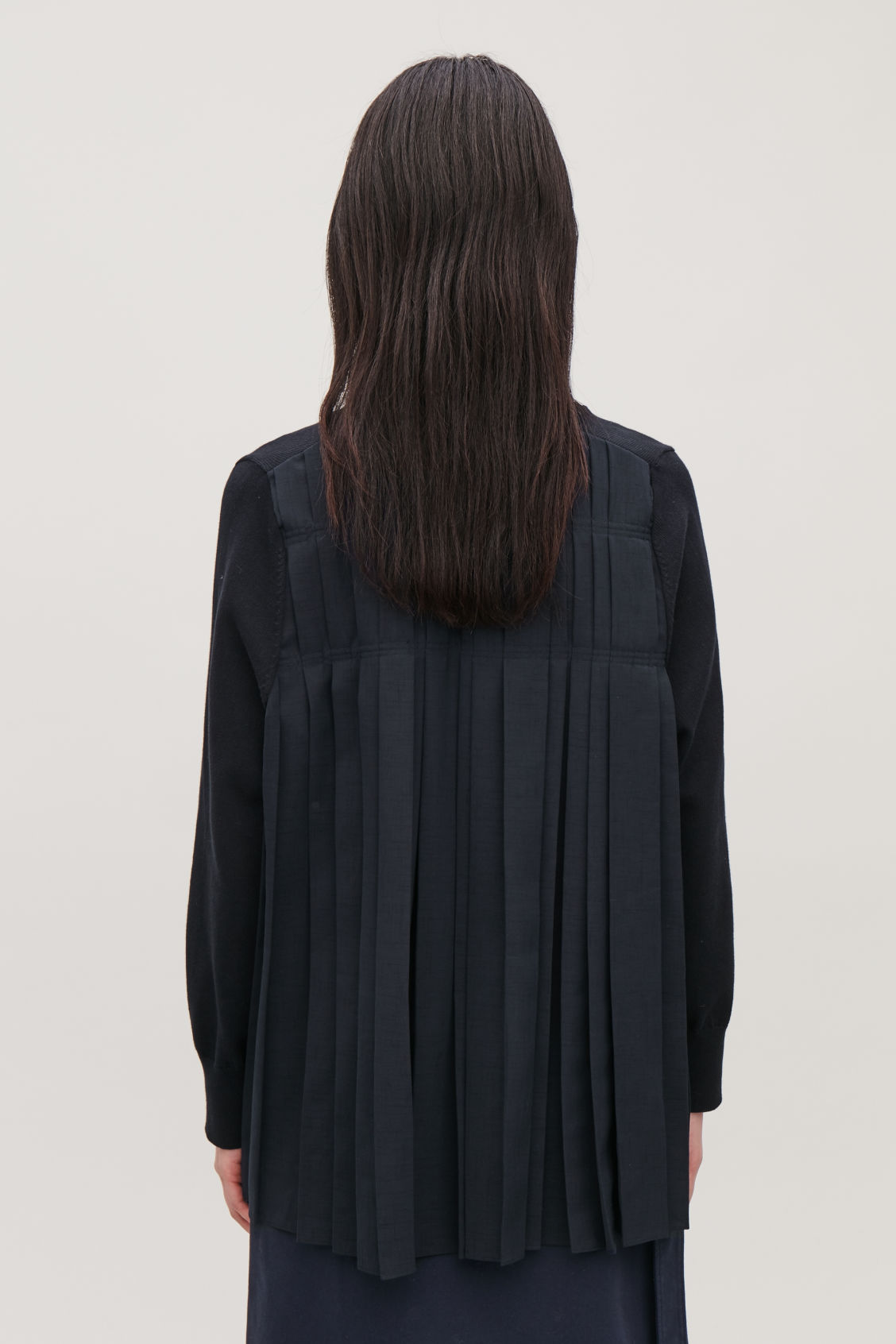 Model side image of Cos pleated-panelled cardigan in blue