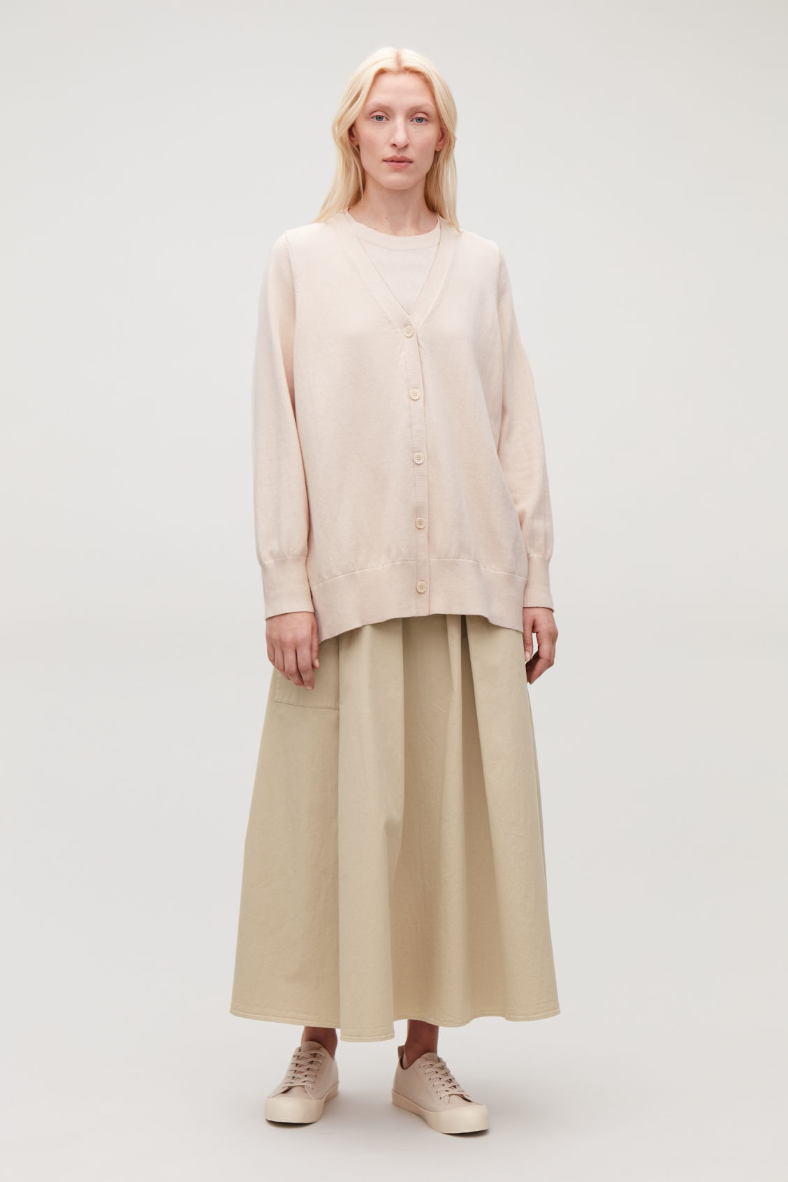 Model side image of Cos pleated-panelled cardigan in beige