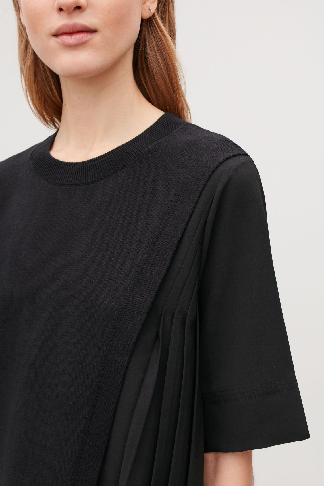 Model side image of Cos pleated-panelled knit dress in black
