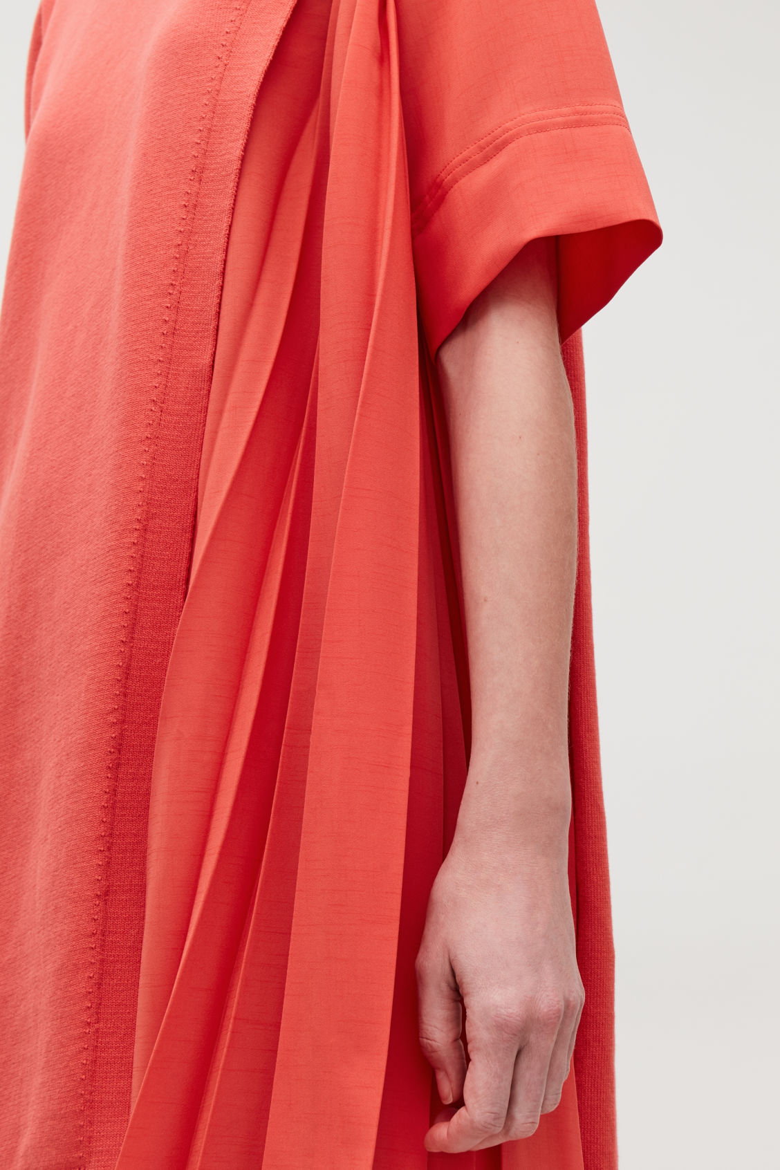 Model side image of Cos pleated-panelled knit dress in orange