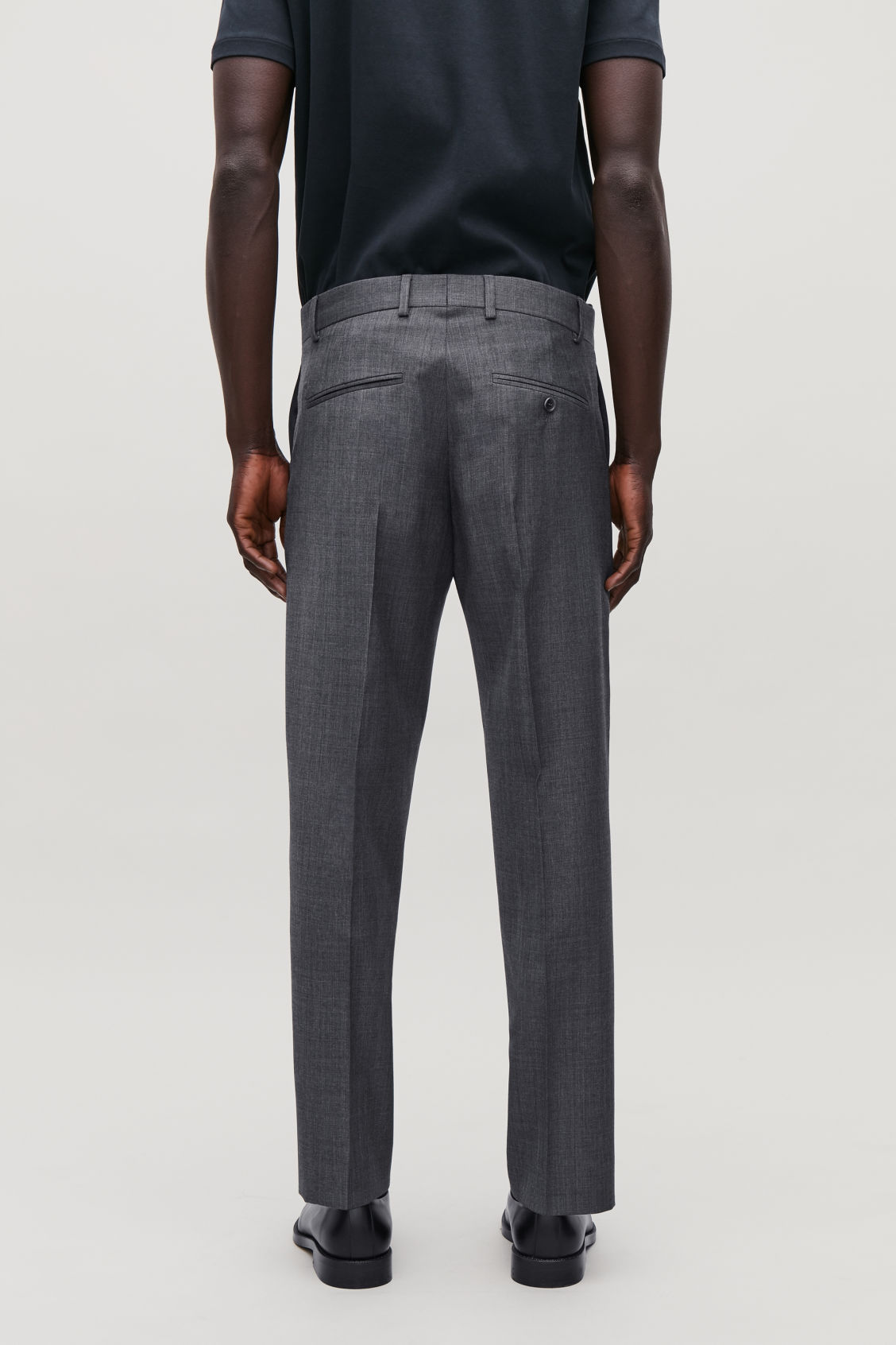 Model side image of Cos slim-fit tailored trousers  in grey