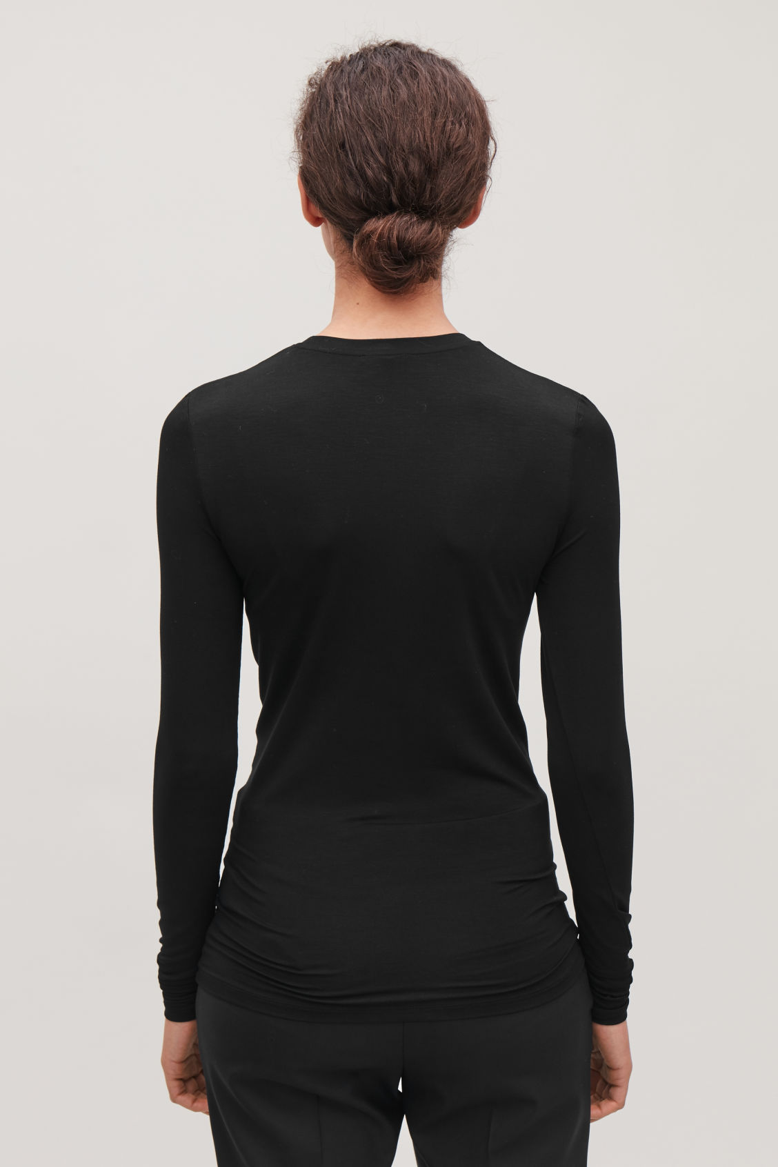 Model side image of Cos slim-fit jersey top in black