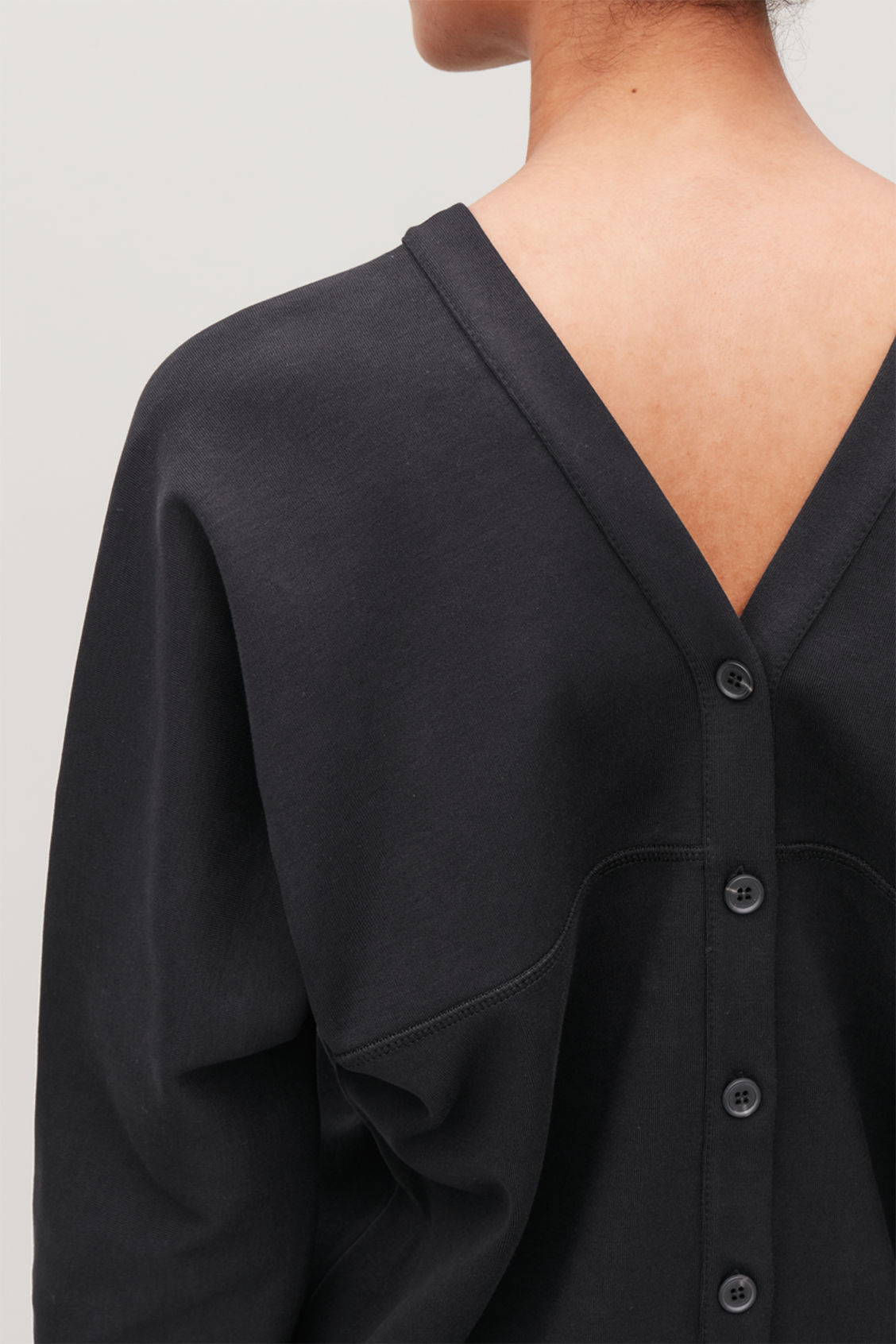 Model side image of Cos deep v-neck jersey top in black