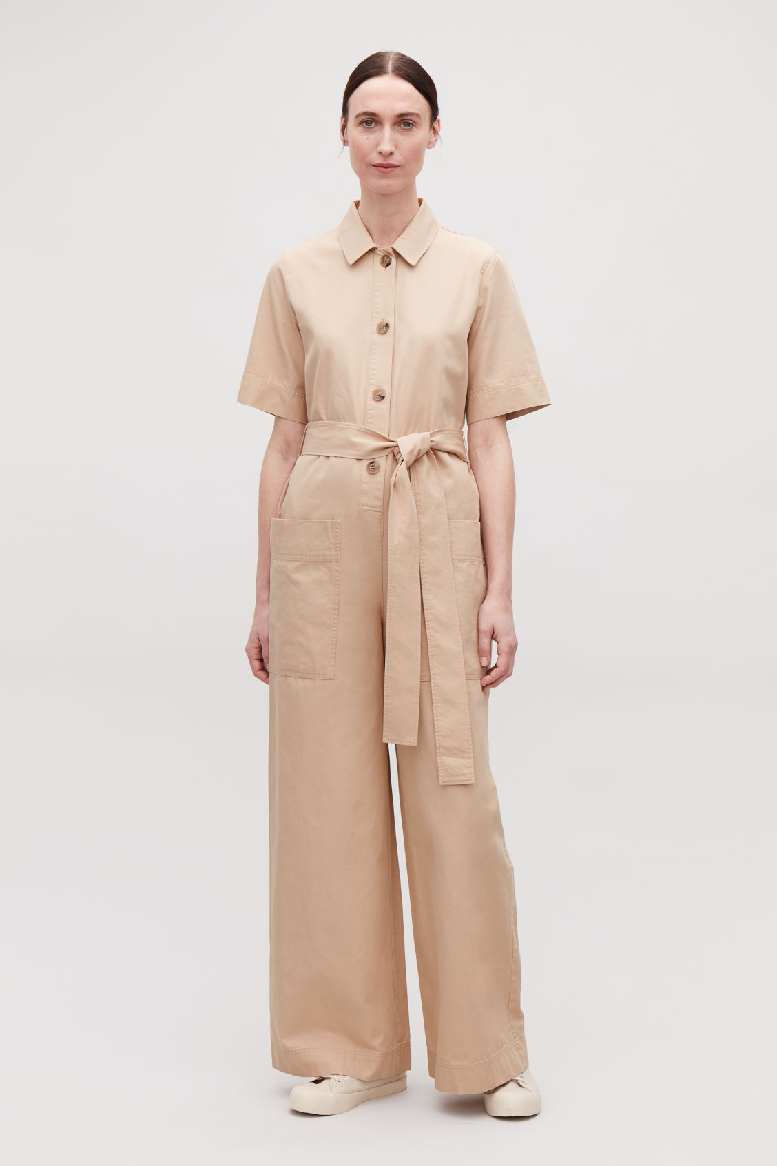 Model front image of Cos belted button-up jumpsuit in beige