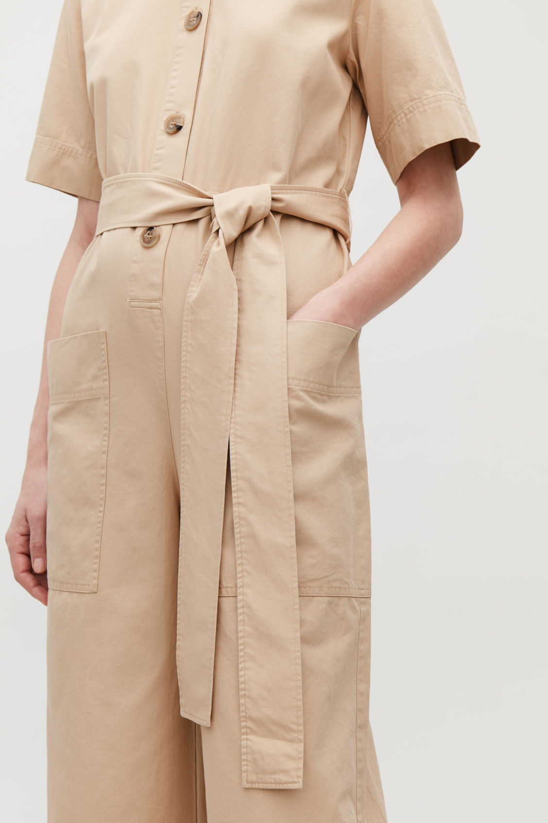 Model side image of Cos belted button-up jumpsuit in beige