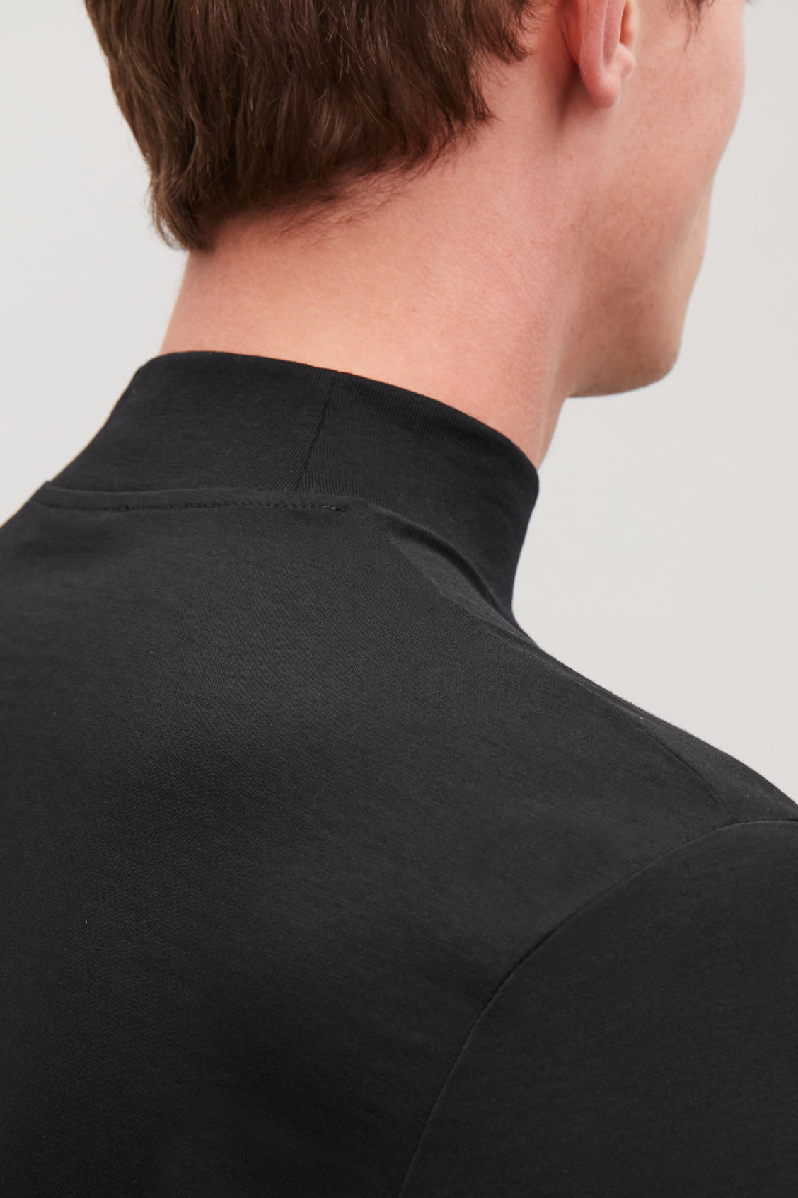 Model side image of Cos cotton jersey roll-neck top in black