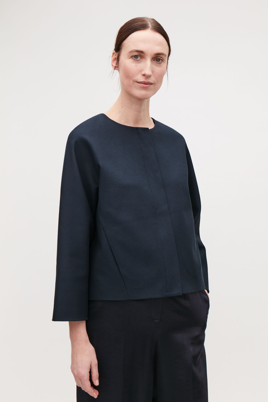 Model side image of Cos collarless zip-up blazer in blue