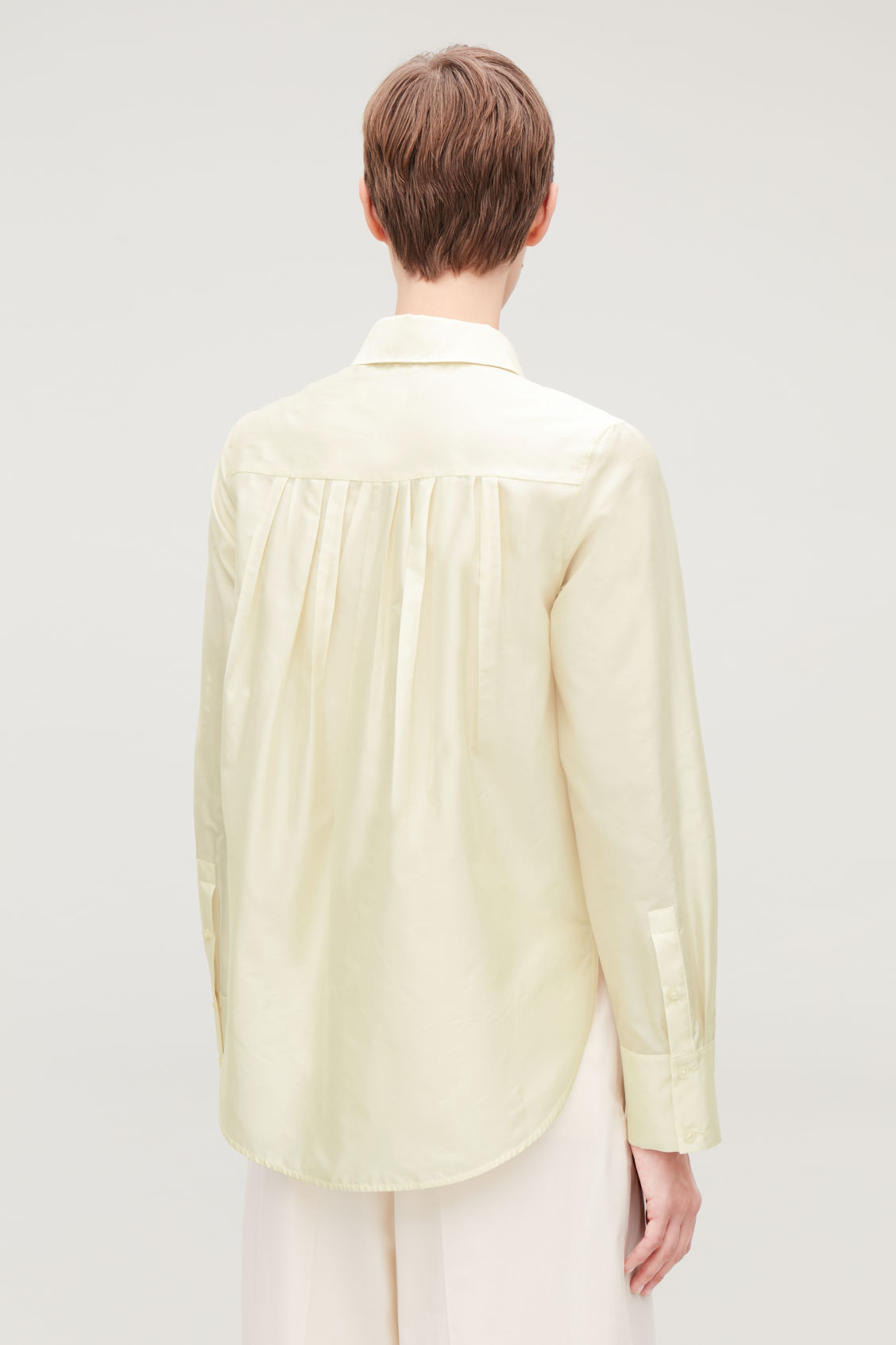 Model side image of Cos silk-blend shirt with box pleats in beige