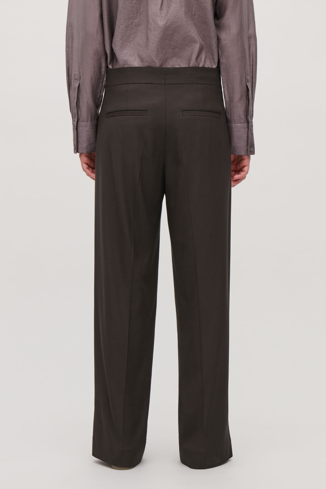 Model side image of Cos vent-detail tailored trousers in brown