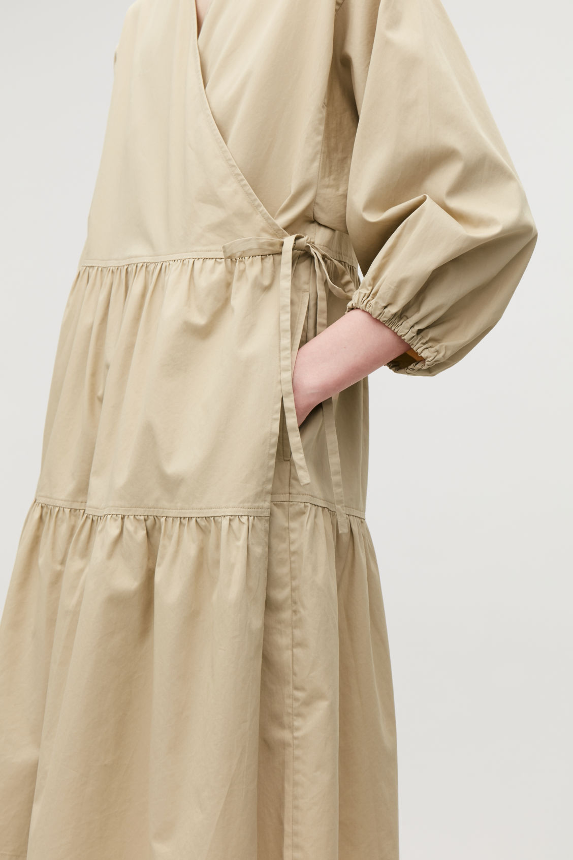 Model side image of Cos gathered a-line wrap dress  in beige