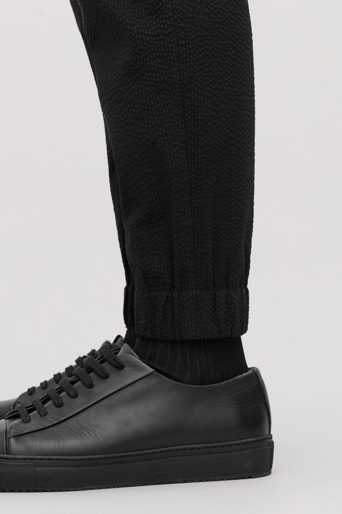 Model side image of Cos relaxed seersucker trousers in black