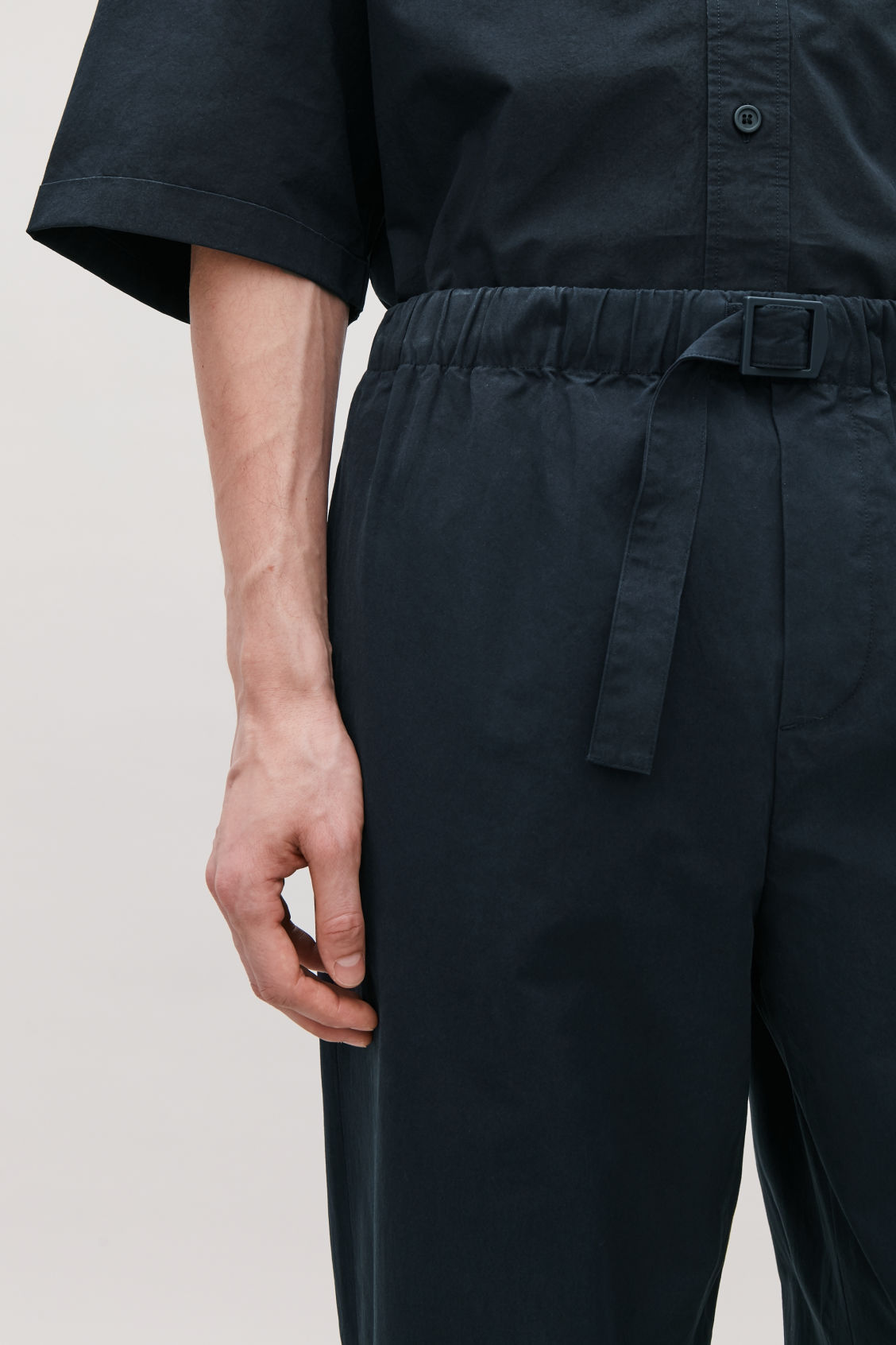 Model side image of Cos relaxed cotton trousers with buckle  in blue