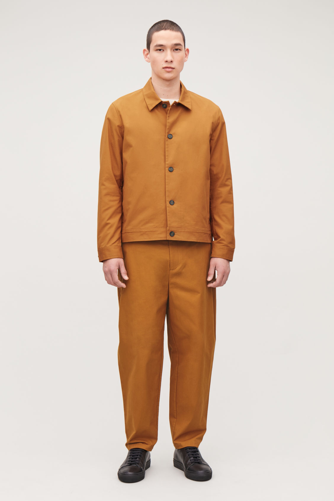Model side image of Cos wide-leg pleated chinos in orange