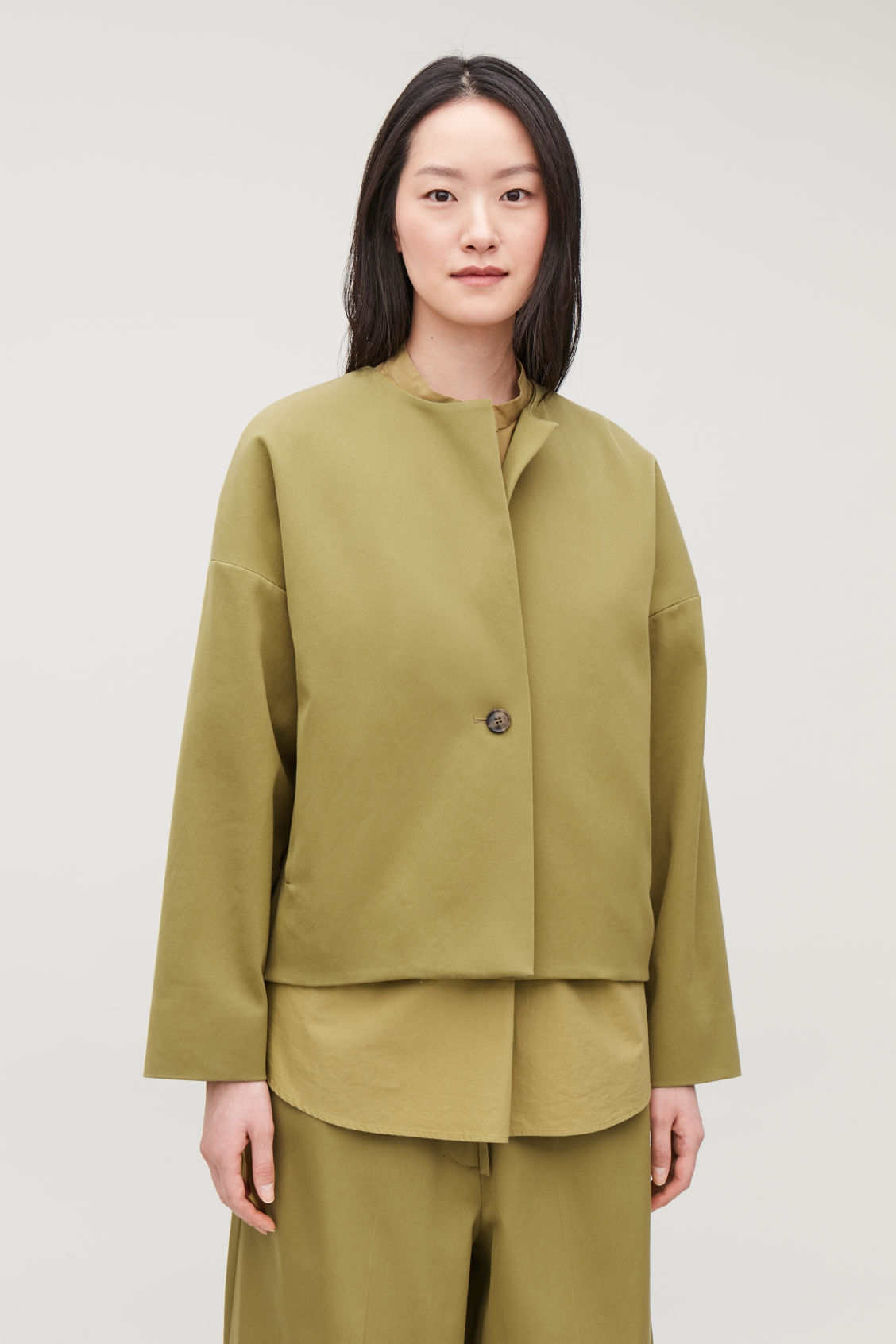 Model side image of Cos boxy a-line cotton jacket in green