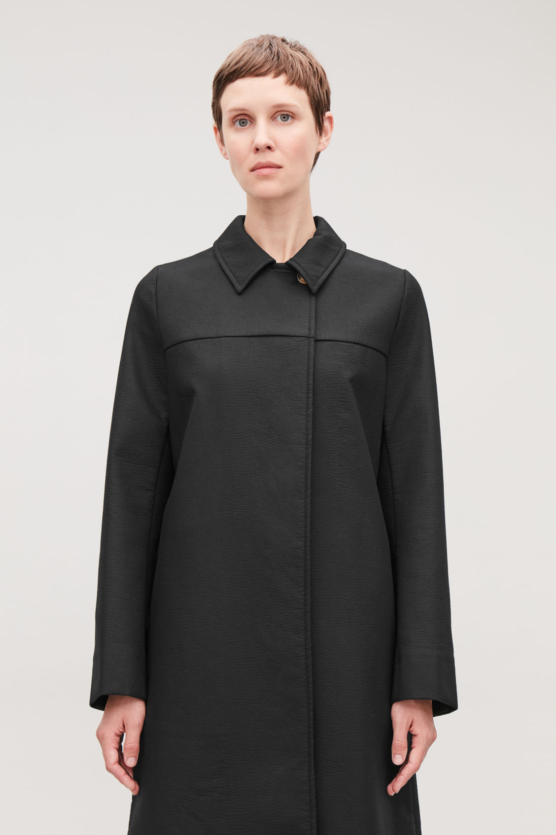 Model side image of Cos long textured-cotton coat  in black