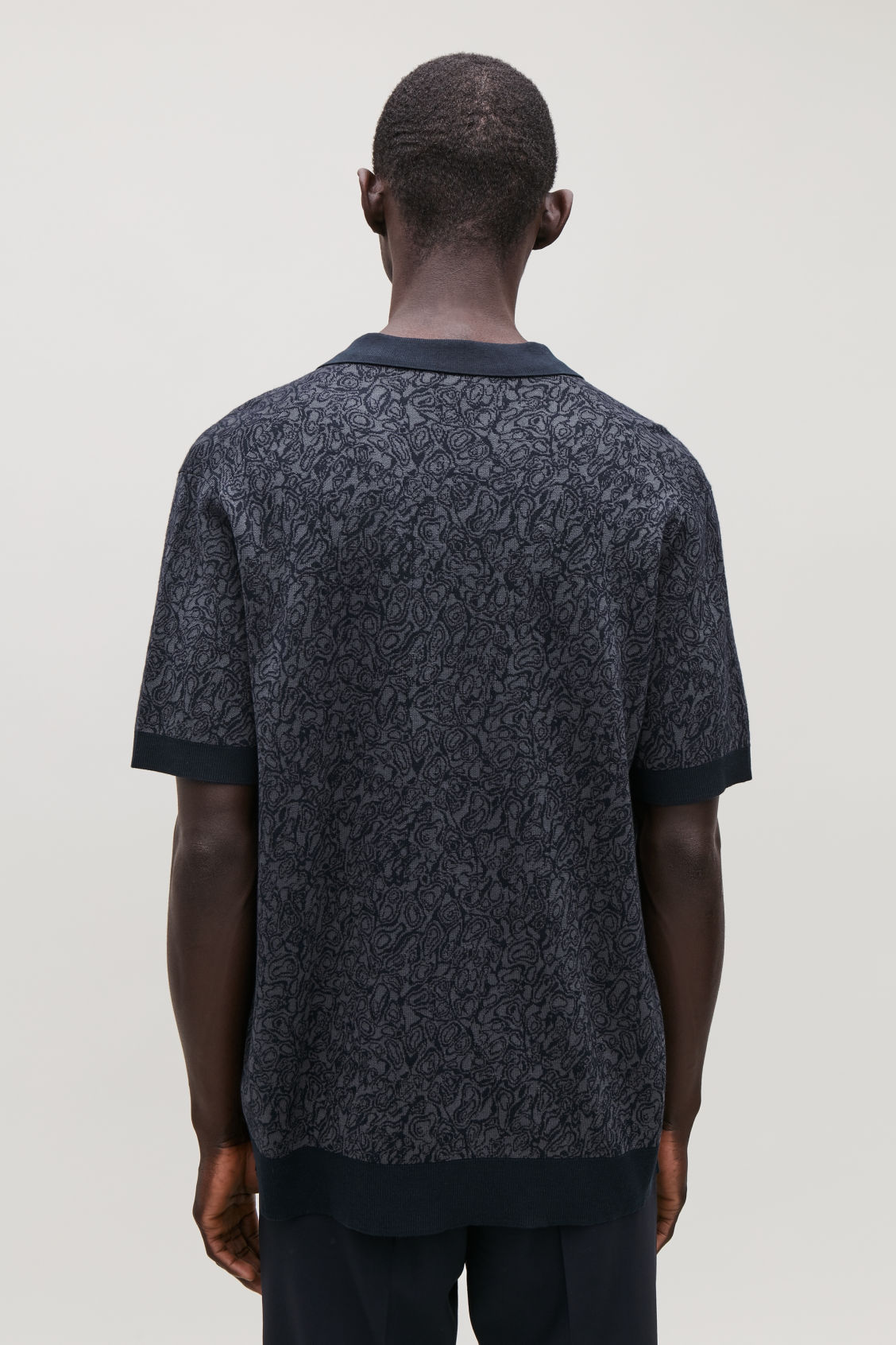 Model side image of Cos marble-print knit polo in grey