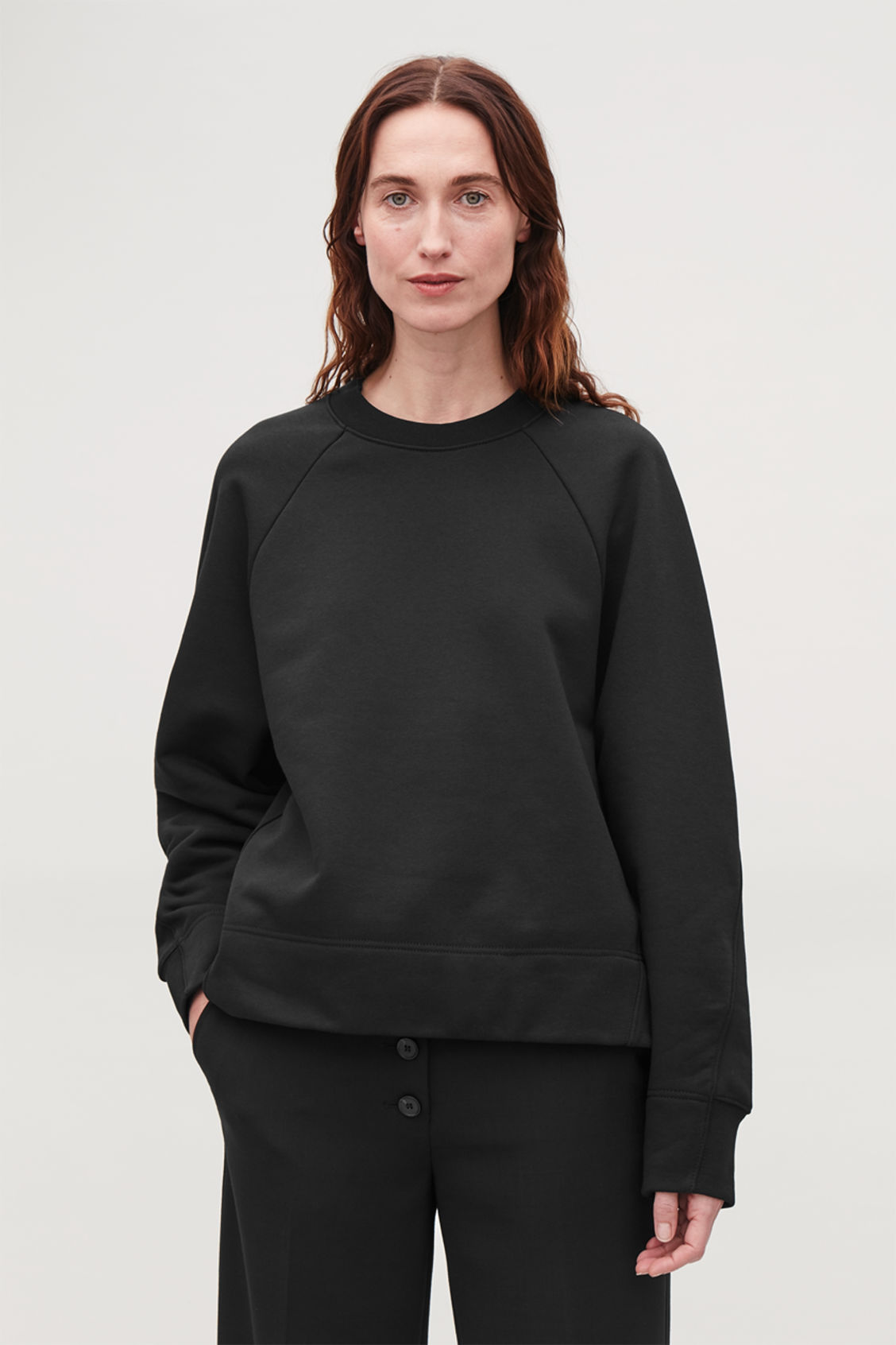 Model side image of Cos sweatshirt with shaped sleeves in black