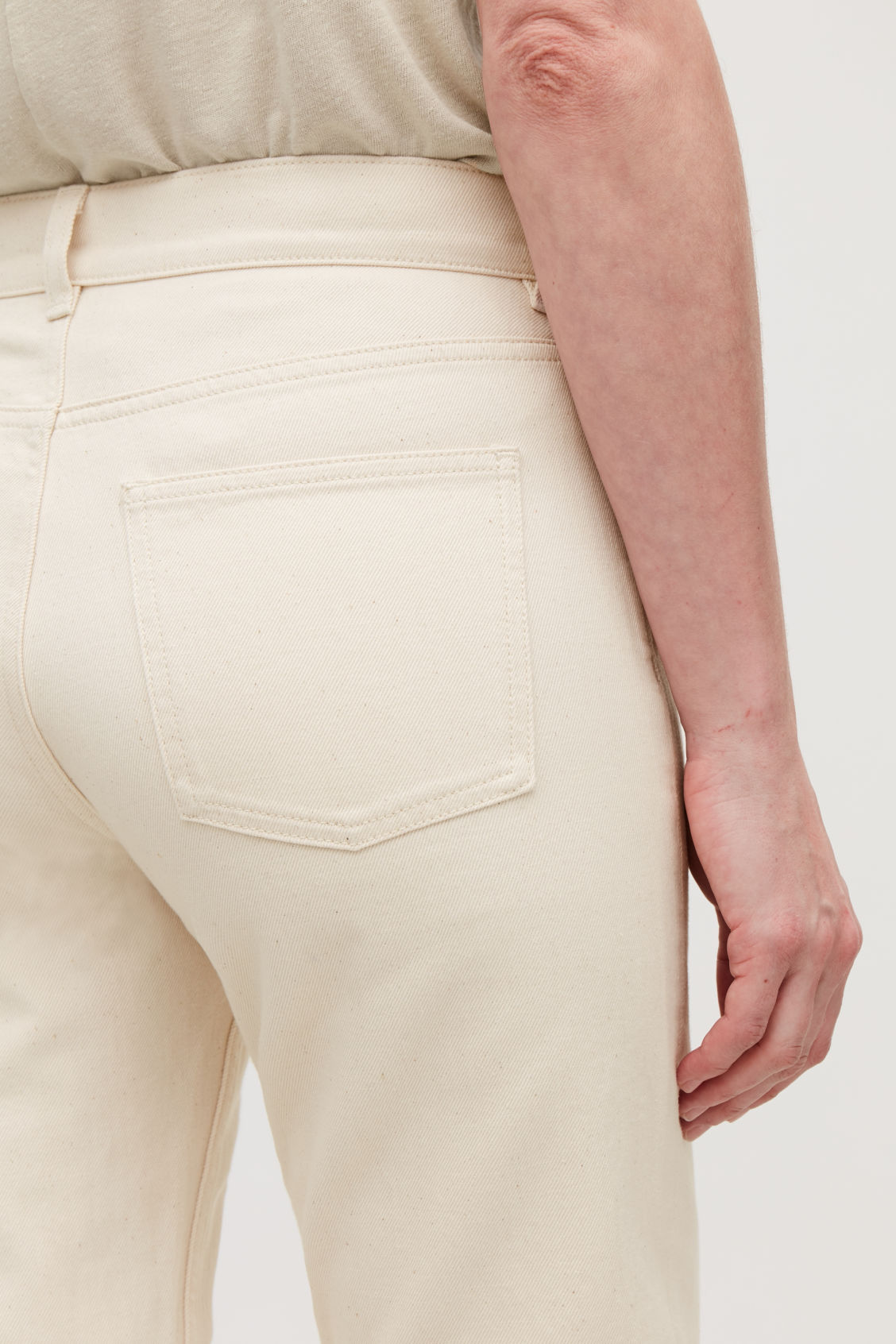 Model side image of Cos slim leg jeans in cream