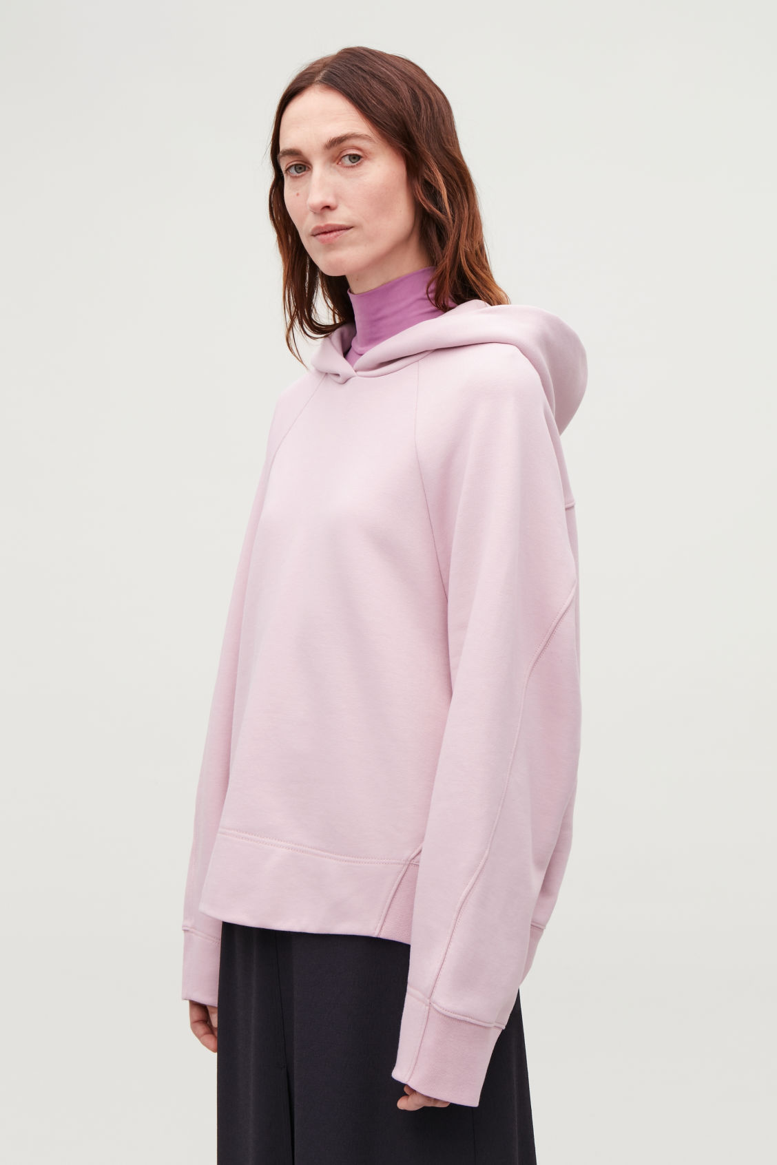 Model side image of Cos hooded sweatshirt with wrap seams in pink