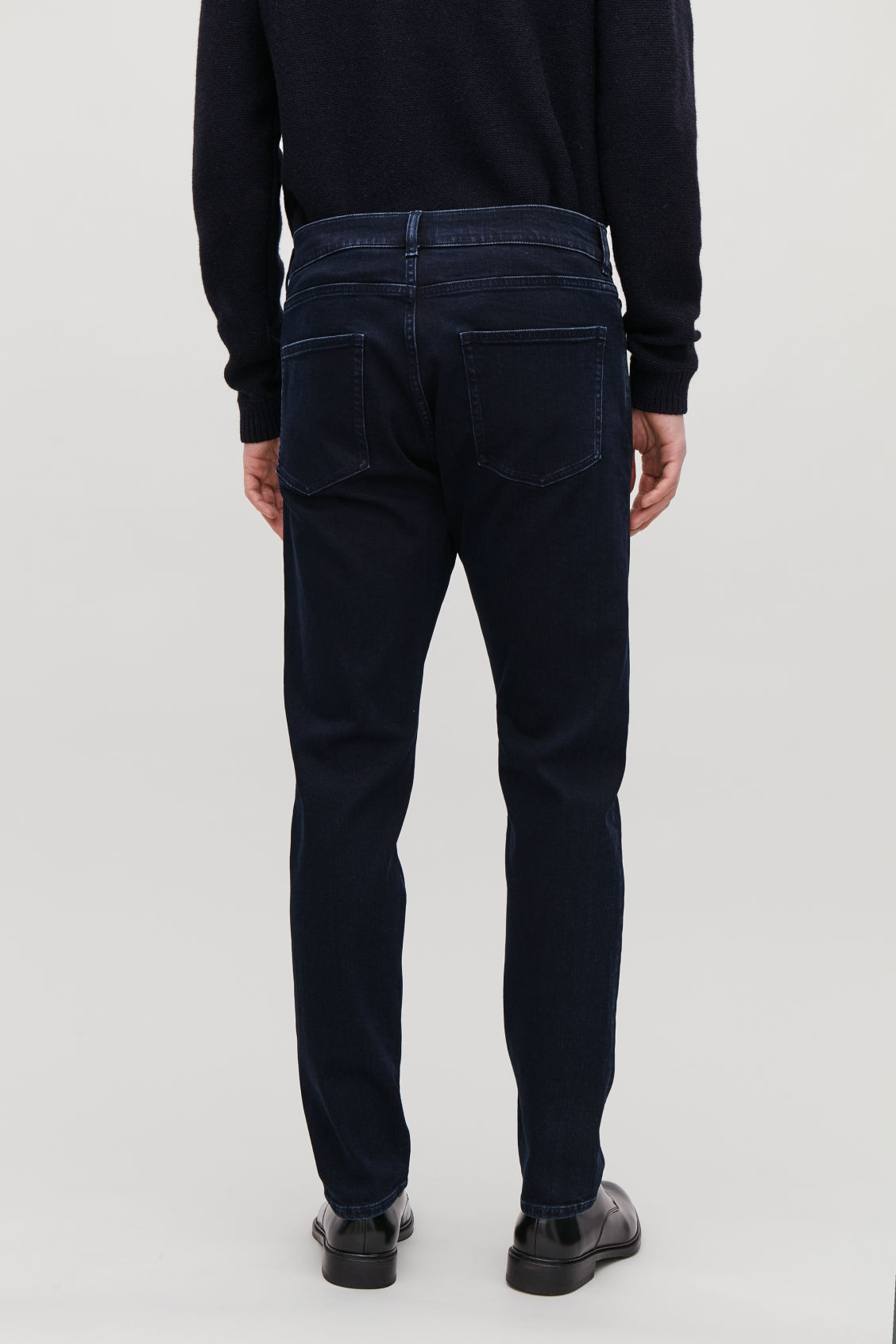 Model side image of Cos slim-leg jeans in blue