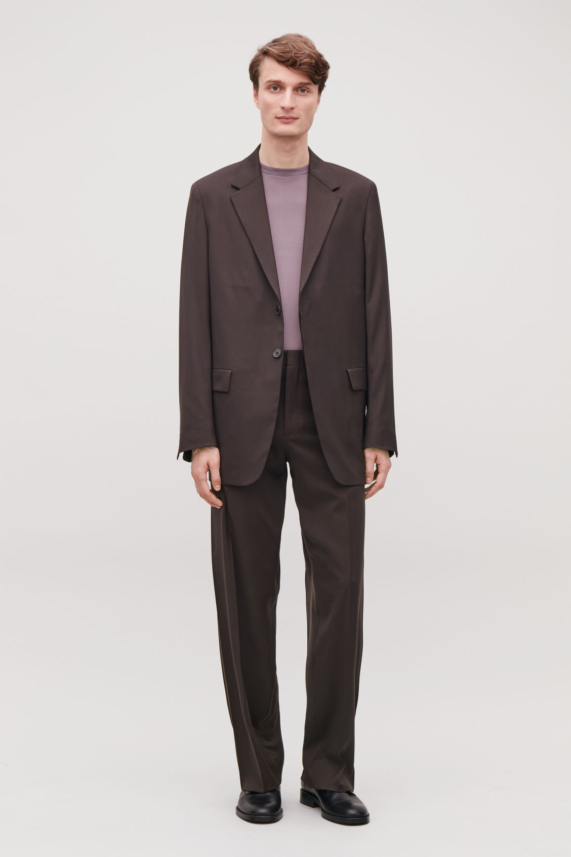 Model side image of Cos relaxed tailored trousers in brown