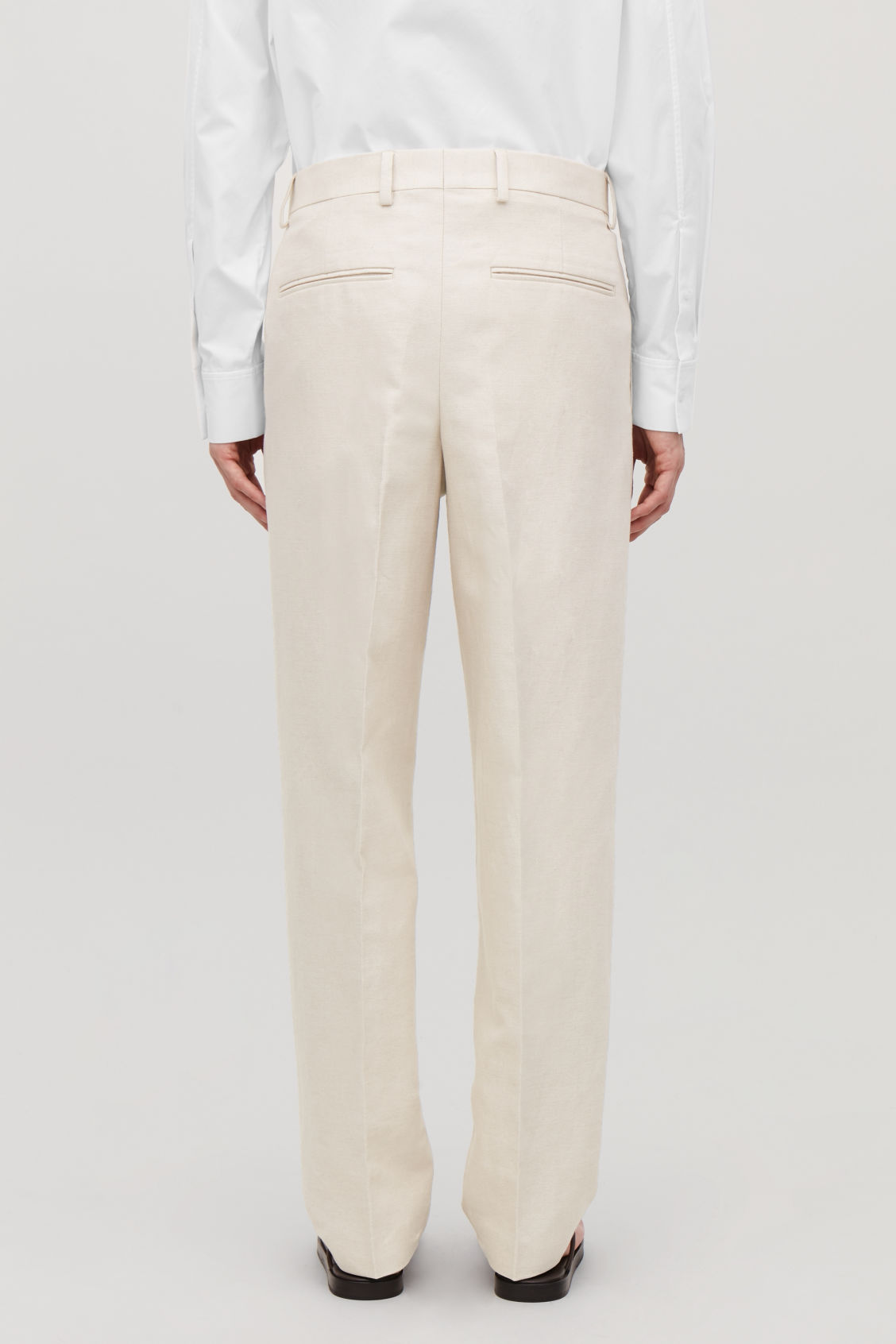 Model side image of Cos straight-leg linen trousers in beige
