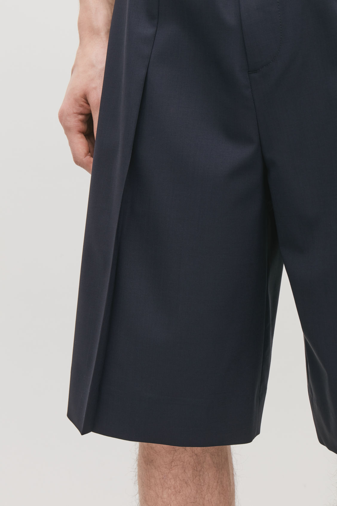 Model side image of Cos pleated tailored shorts in blue