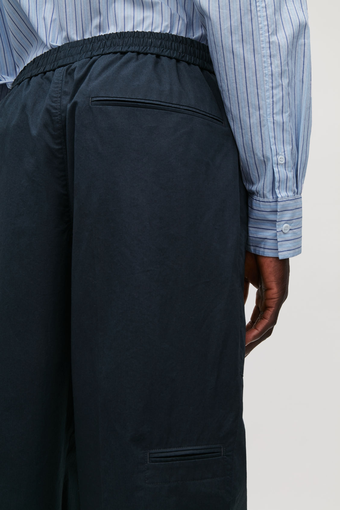 Model side image of Cos cargo trousers with jet pockets in blue