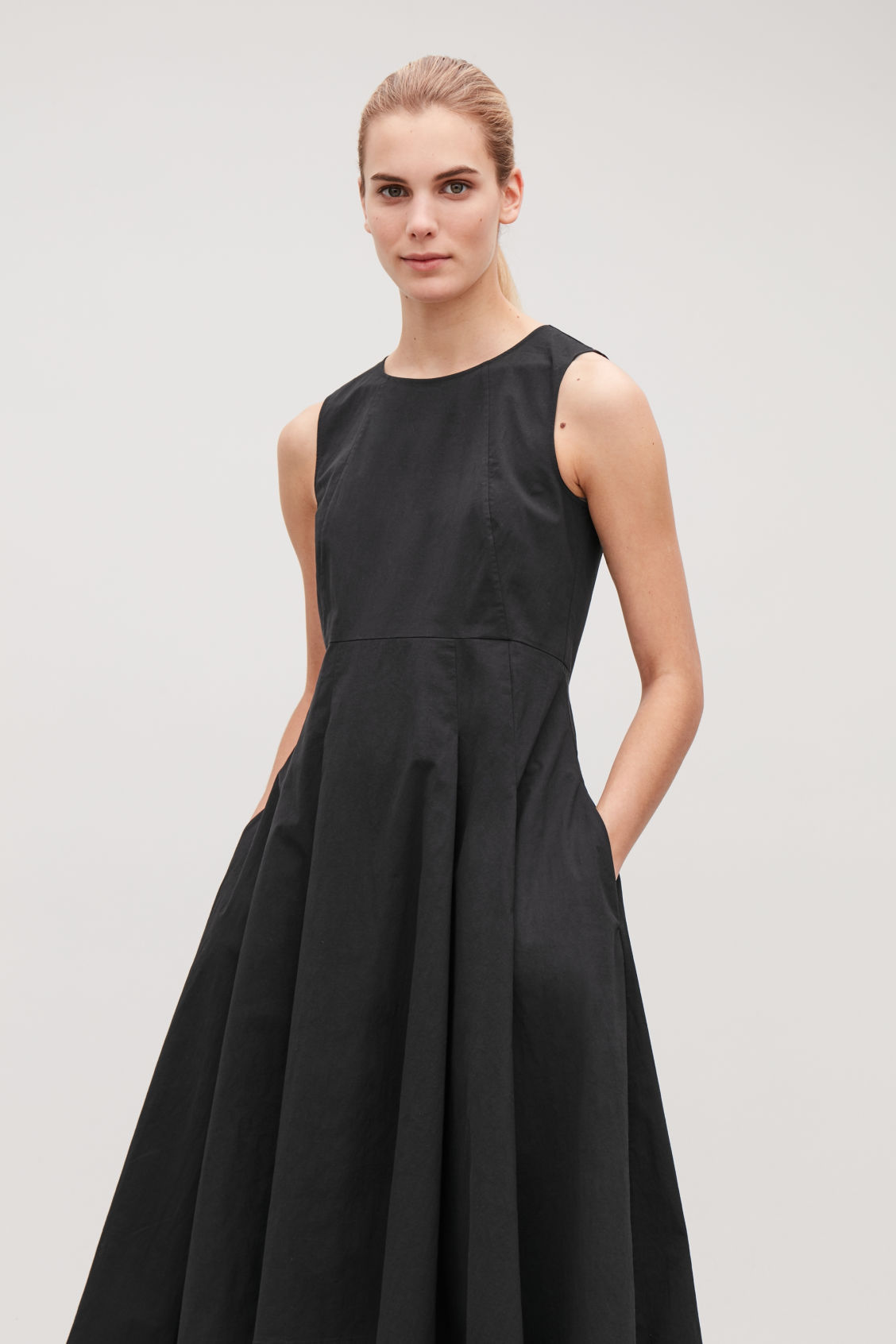 Model side image of Cos waisted dress with pleats  in black