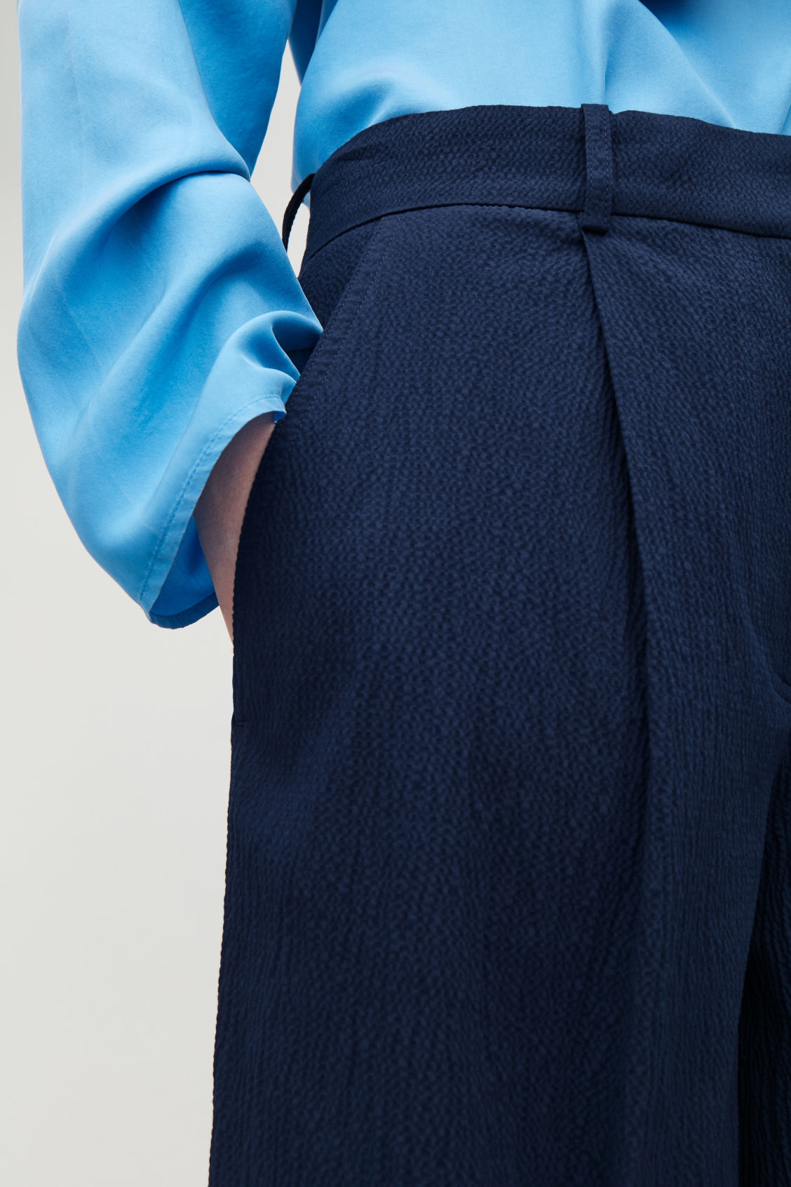 Model side image of Cos wide-leg seersucker trousers in blue