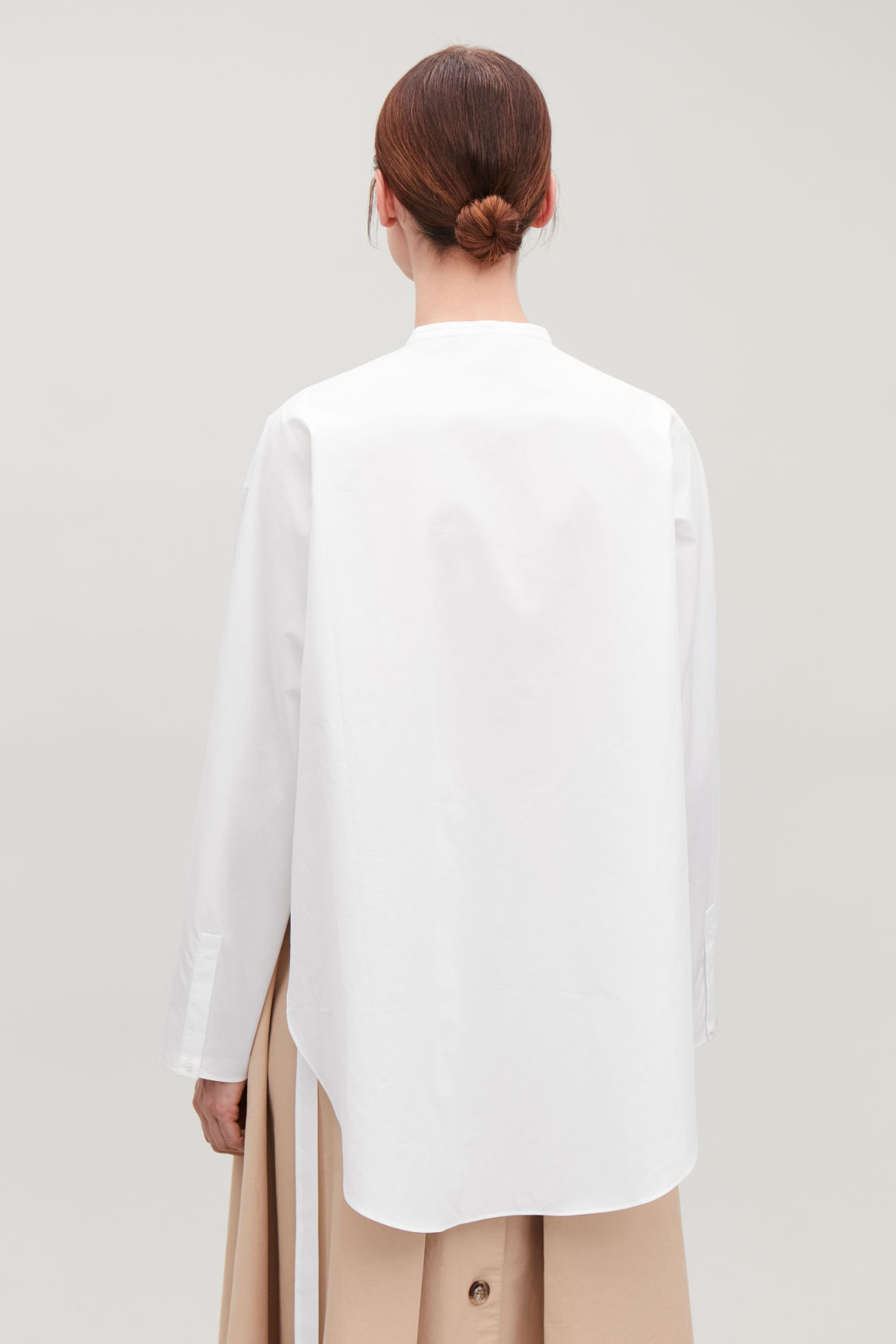 Model side image of Cos tie-waist bib-front shirt in white