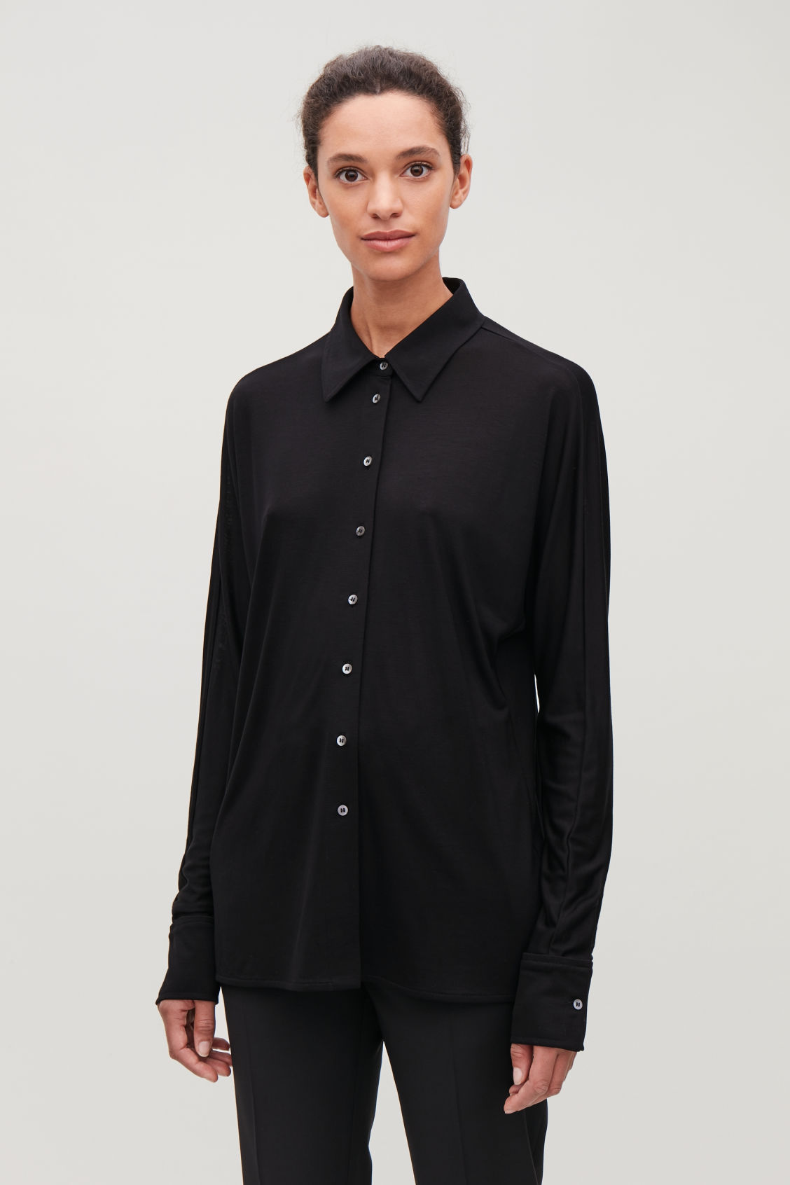 Model side image of Cos batwing-sleeved jersey shirt in black