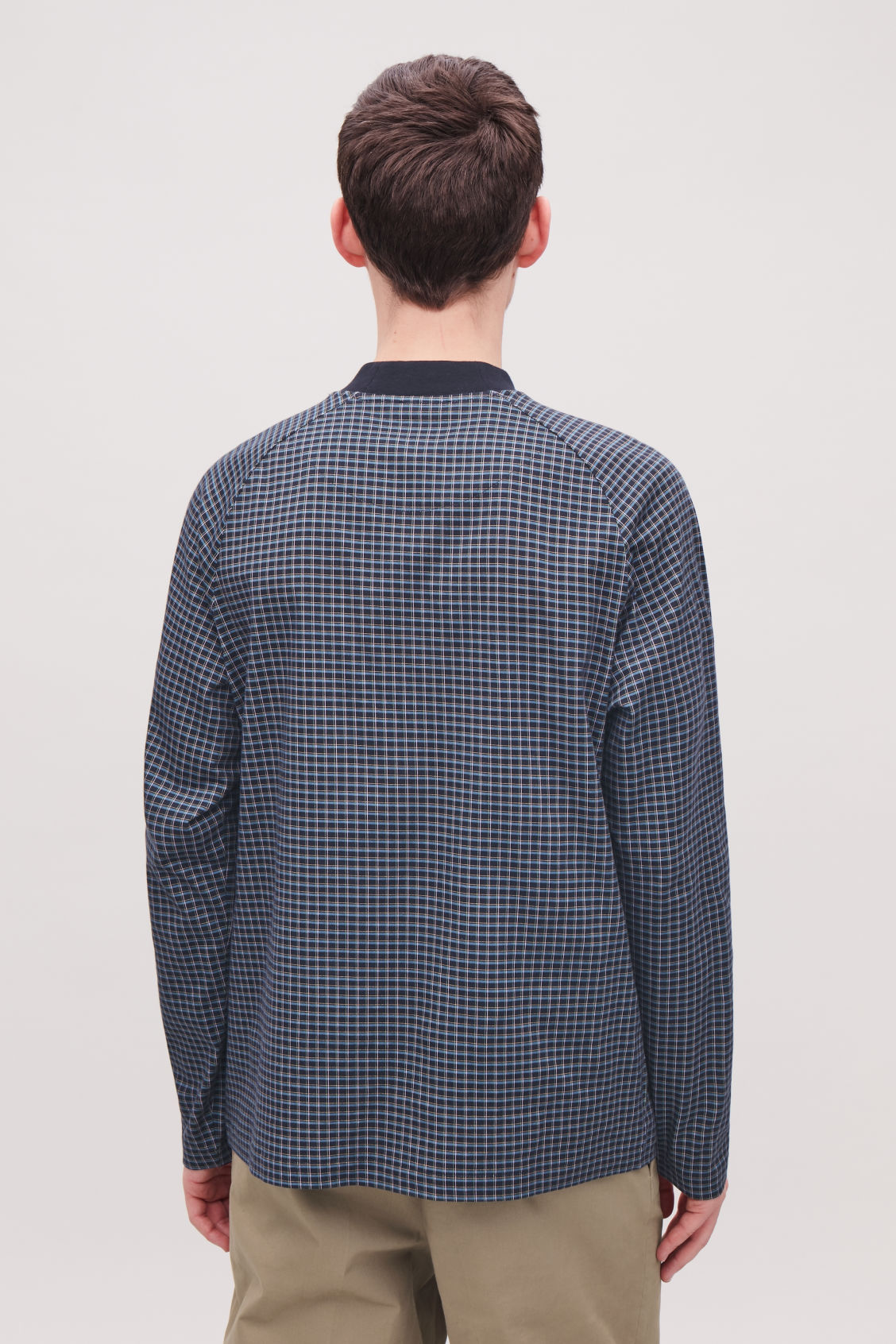 Model side image of Cos relaxed check sweatshirt in blue