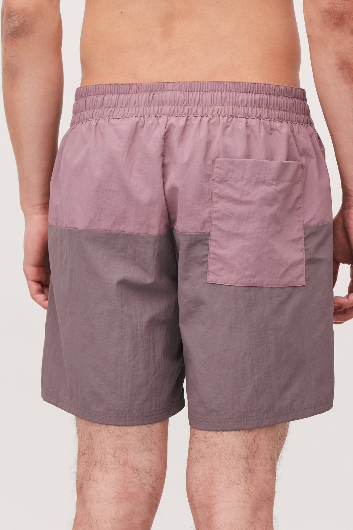 Model side image of Cos colour-block swim shorts in purple