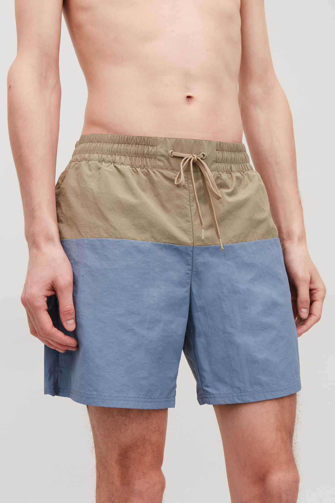 Model side image of Cos colour-block swim shorts in blue