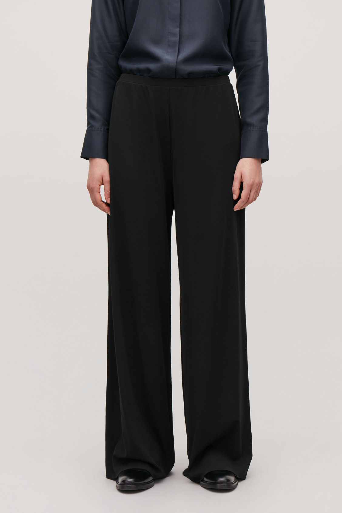 Model side image of Cos relaxed elastic-waist trousers in black