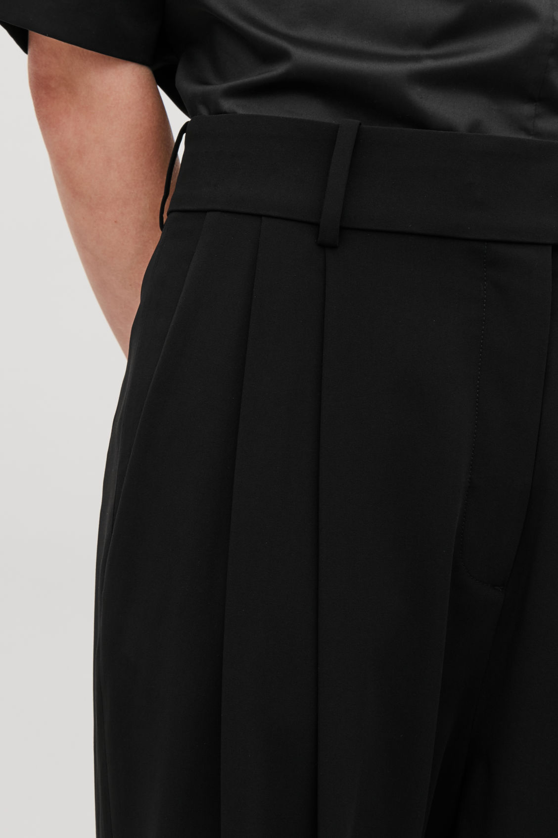 Model side image of Cos relaxed pleated trousers in black
