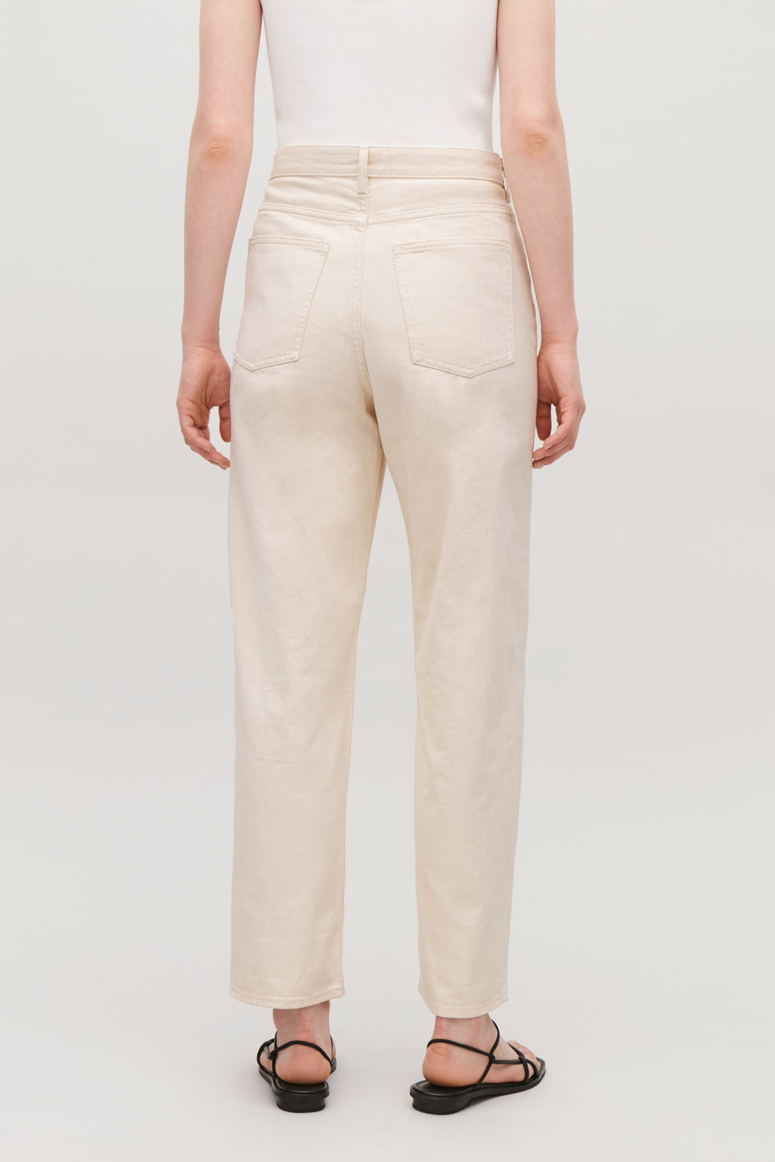 Model side image of Cos tapered leg jeans in white