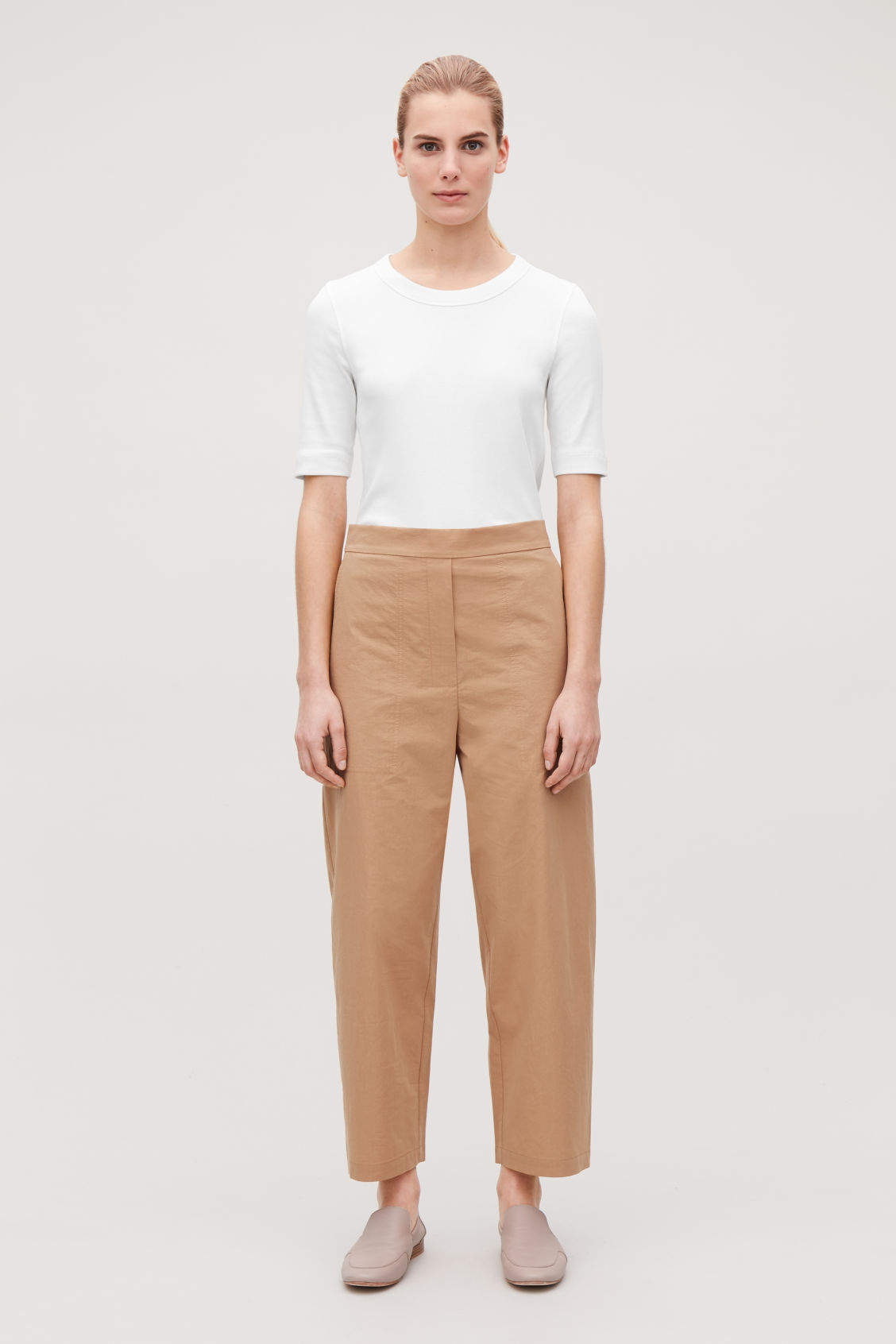 Model front image of Cos relaxed-fit cotton chinos in beige