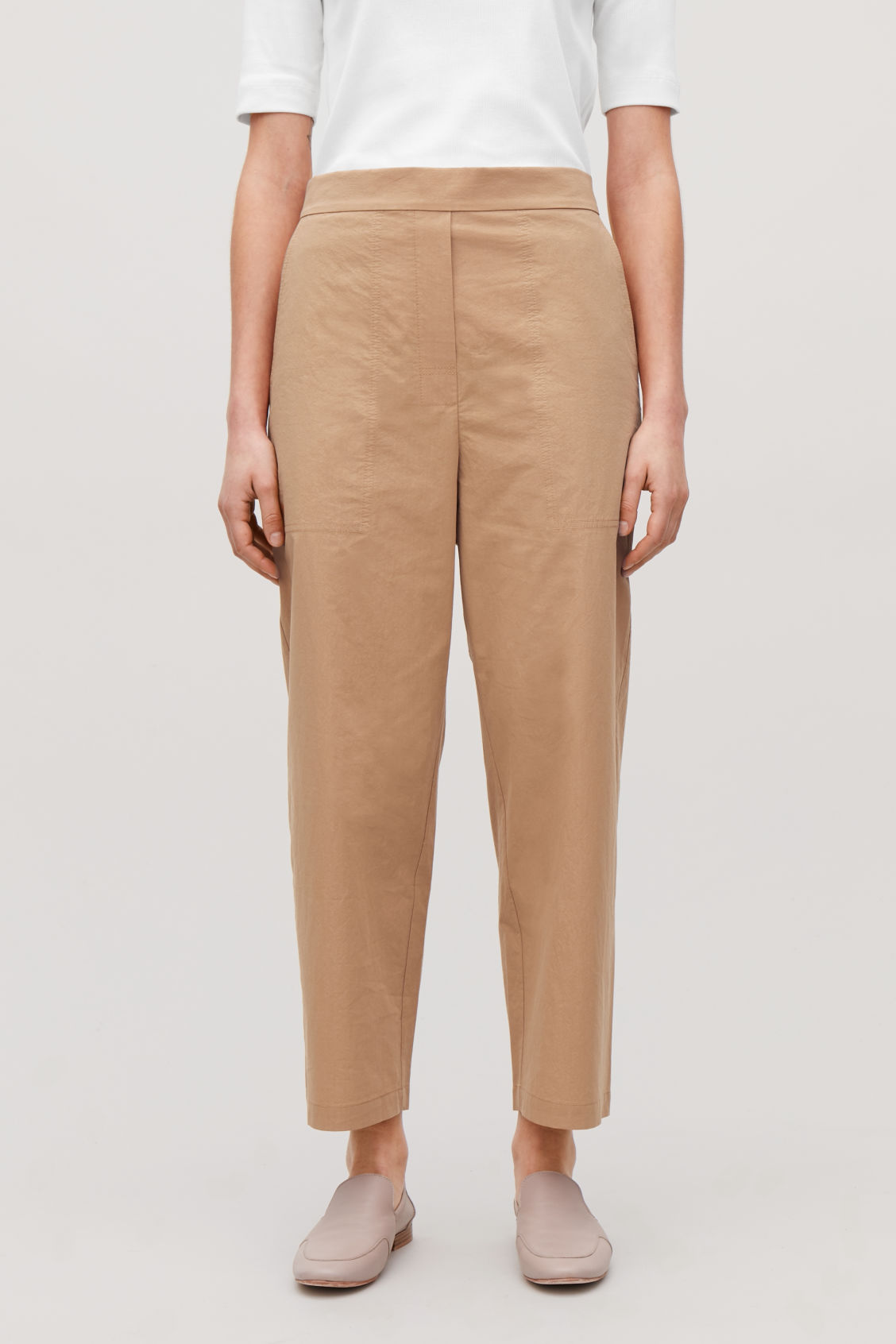 Model side image of Cos relaxed-fit cotton chinos in beige