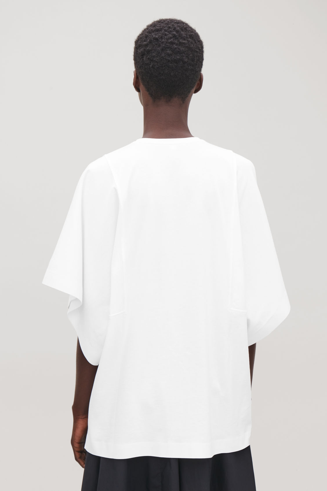 Model side image of Cos kimono-sleeved jersey top in white
