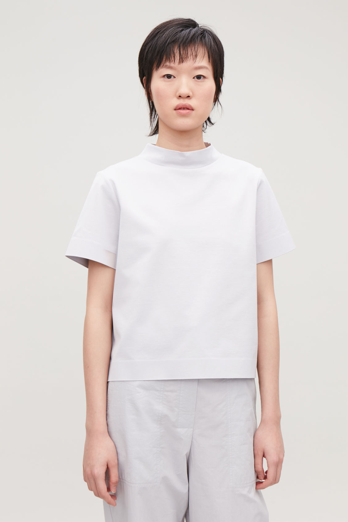 Model side image of Cos boxy mock-neck jersey top in grey