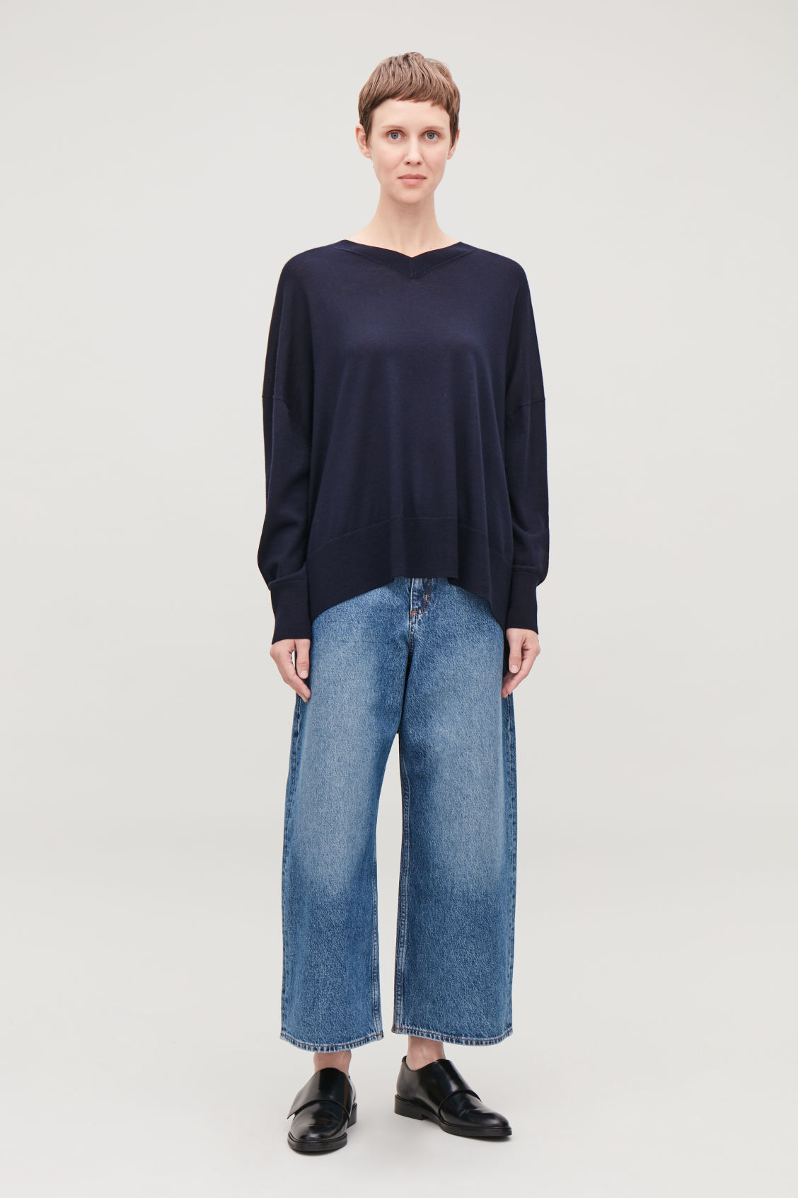 Model side image of Cos draped merino v-neck jumper in blue