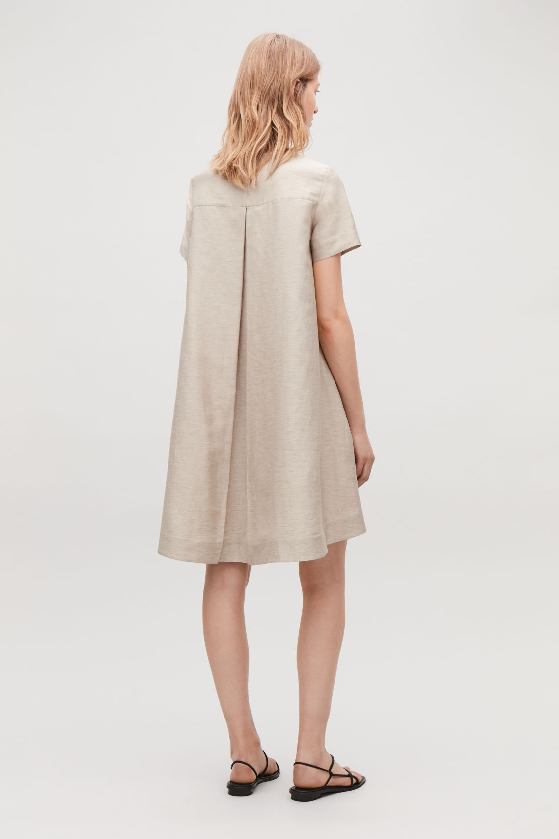 Model side image of Cos linen dress with pleated back in beige