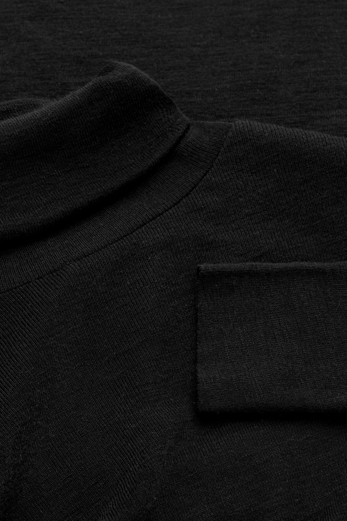 Side image of Cos roll-neck wool top in black